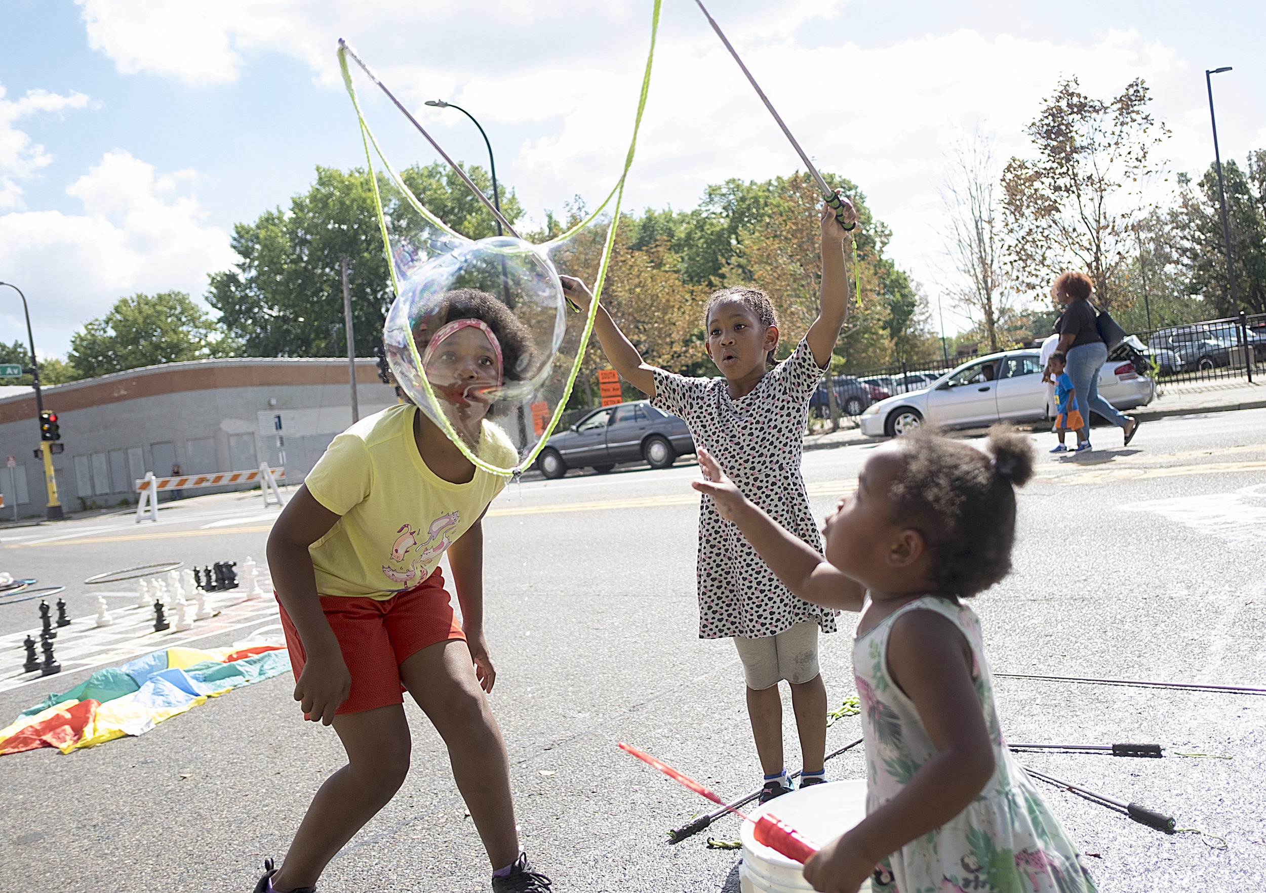 A late summer blast of heat did little to keep people from singing, dancing and laughing with friends and family on Saturday, Sept. 15 during West Broadway Open Streets. Here, Lynea Brown, 10, left, blows to release a soapy bubble drawn by her sister, Georgia, 7, while younger sister Korva reaches out to touch it on the corner of Broadway and Knox.