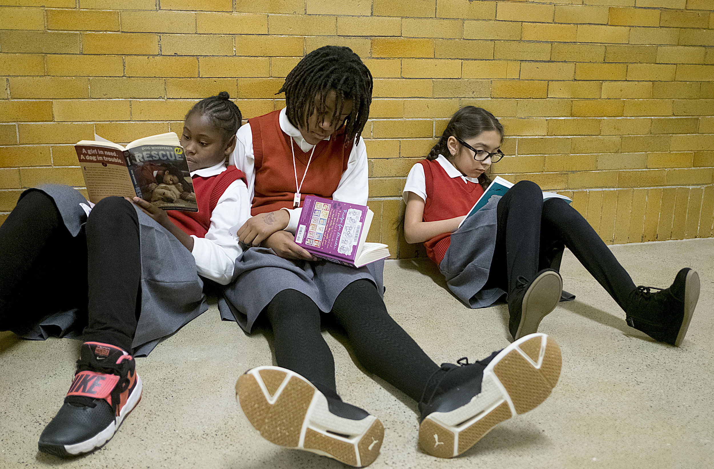 Nancia Buchanan leans into Patience Epps while they read quietly in a hallway with Shelly Marquez Sanchez at Ascension School.