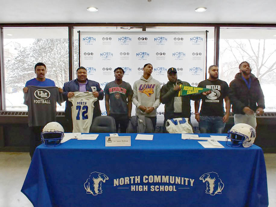Seven North High Senior football players pose with gear representing their future colleges. From left to right: Kehyan Porter, Jaylen Watson, Kawntel Jackson, Omar Brown, Jeremiah Stewart, Izaiah Yeager, and Ar'mon Dalton.  Photo courtesy of Carrie Yeager