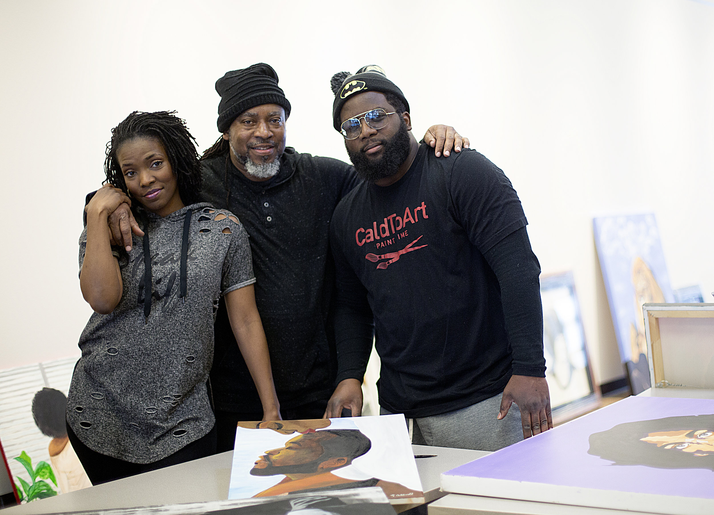 Charles Caldwell (center) and his children, Nakesha (left) and Kenneth (right) pose amidst their paintings as they hung their Black History Month art show at UROC.