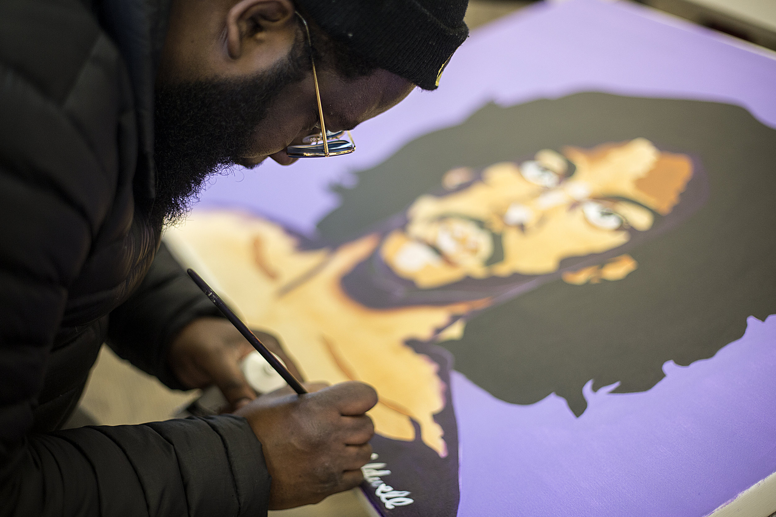 Kenneth Caldwell touches up his well-known painting of Prince.