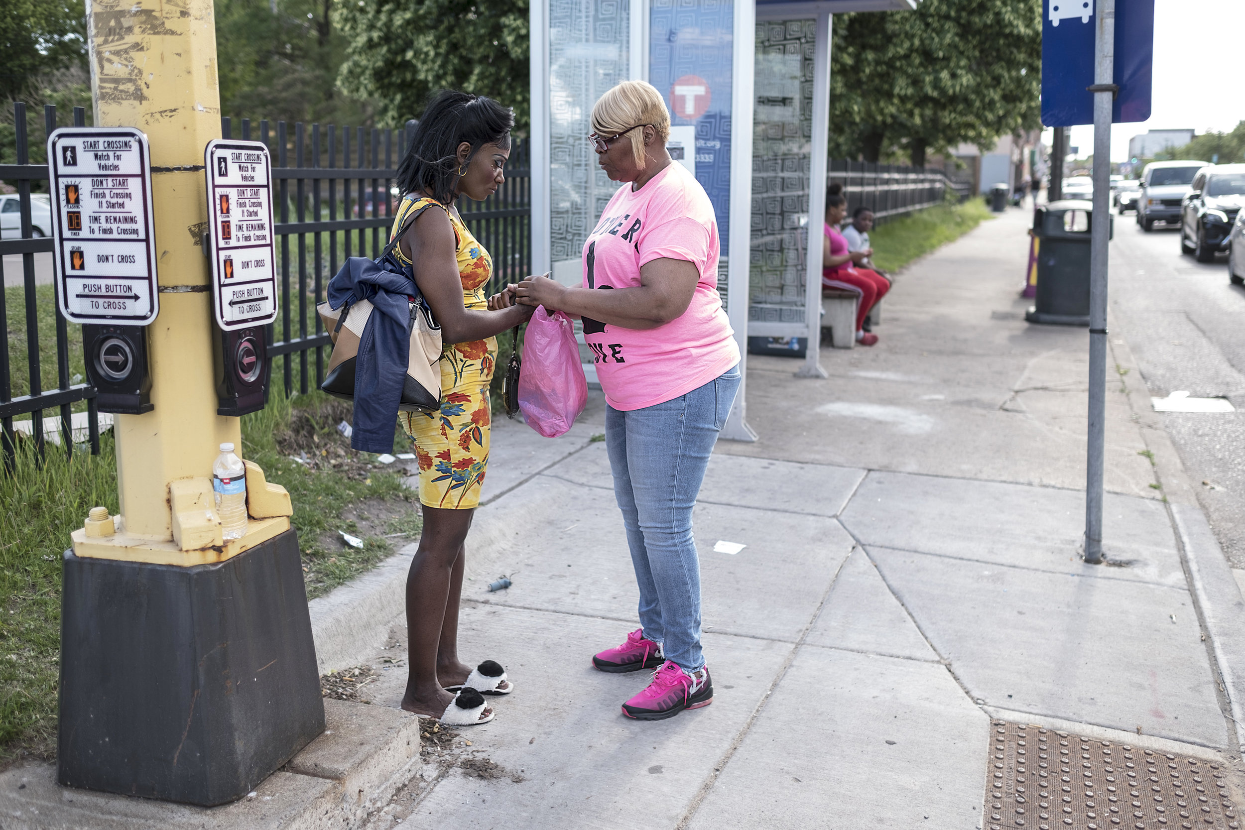 After talking for several minutes, Nona Champion offers to pray with a woman she met near a bus stop on W Broadway Ave.