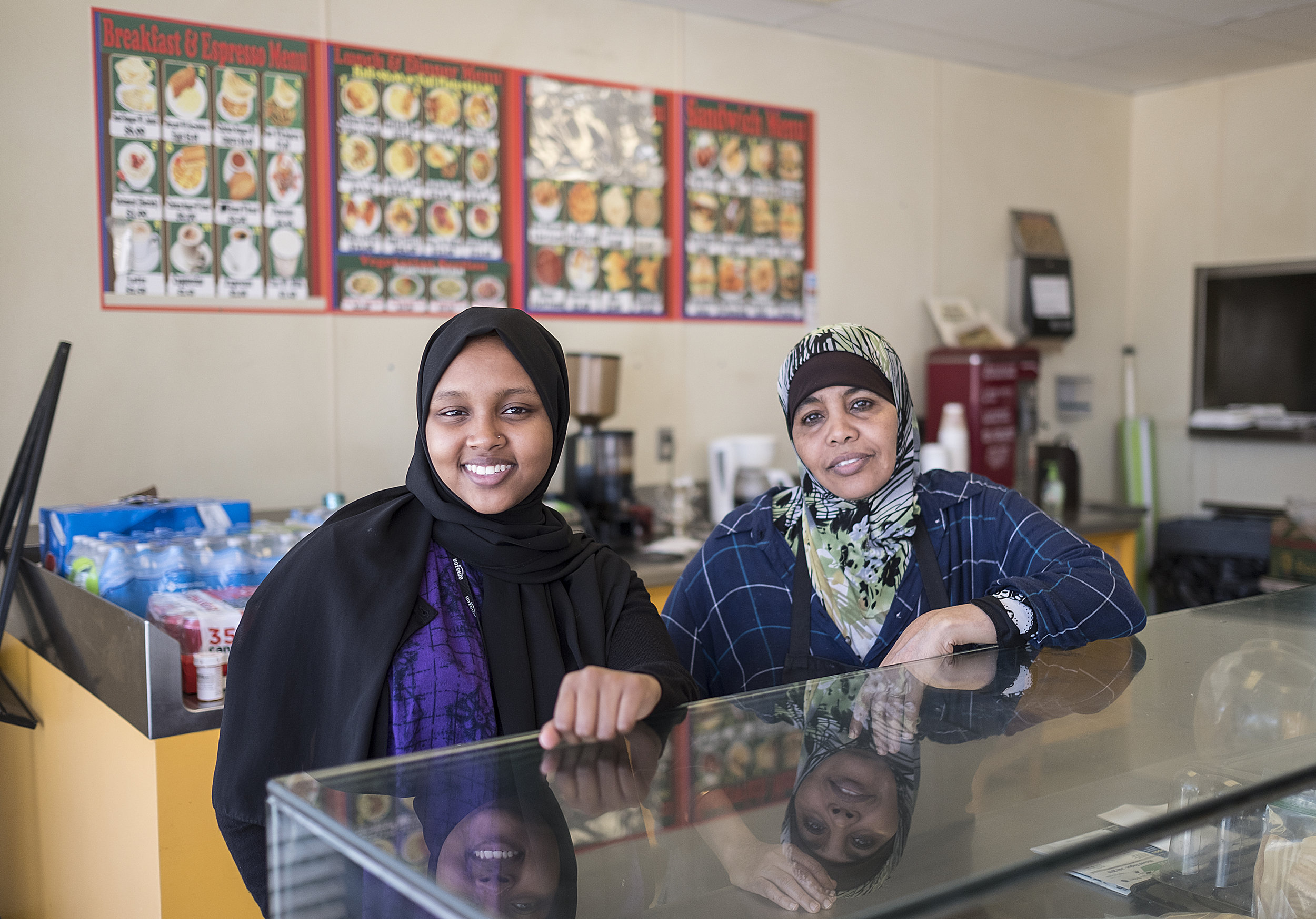 Raniya Sheikh, left, and her mother, Sahra Hassan at the counter of Mama Sahra's Kitchen on Glenwood Avenue.  Photo by David Pierini