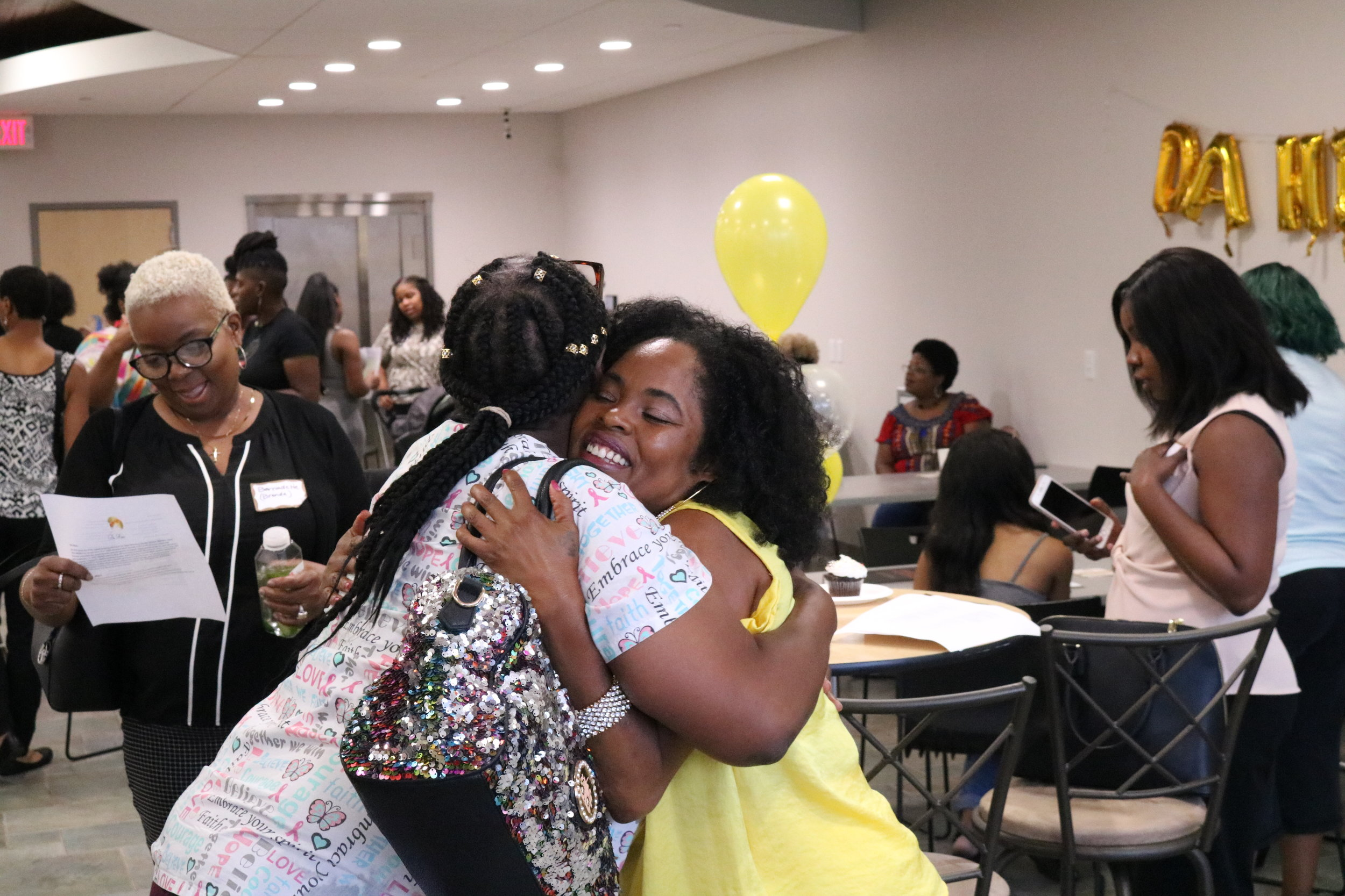 Kenya McKnight (right) embraces family, friends, and colleagues as she celebrates the launch of Da Hive, a coworking space for black women to gain economic empowerment.