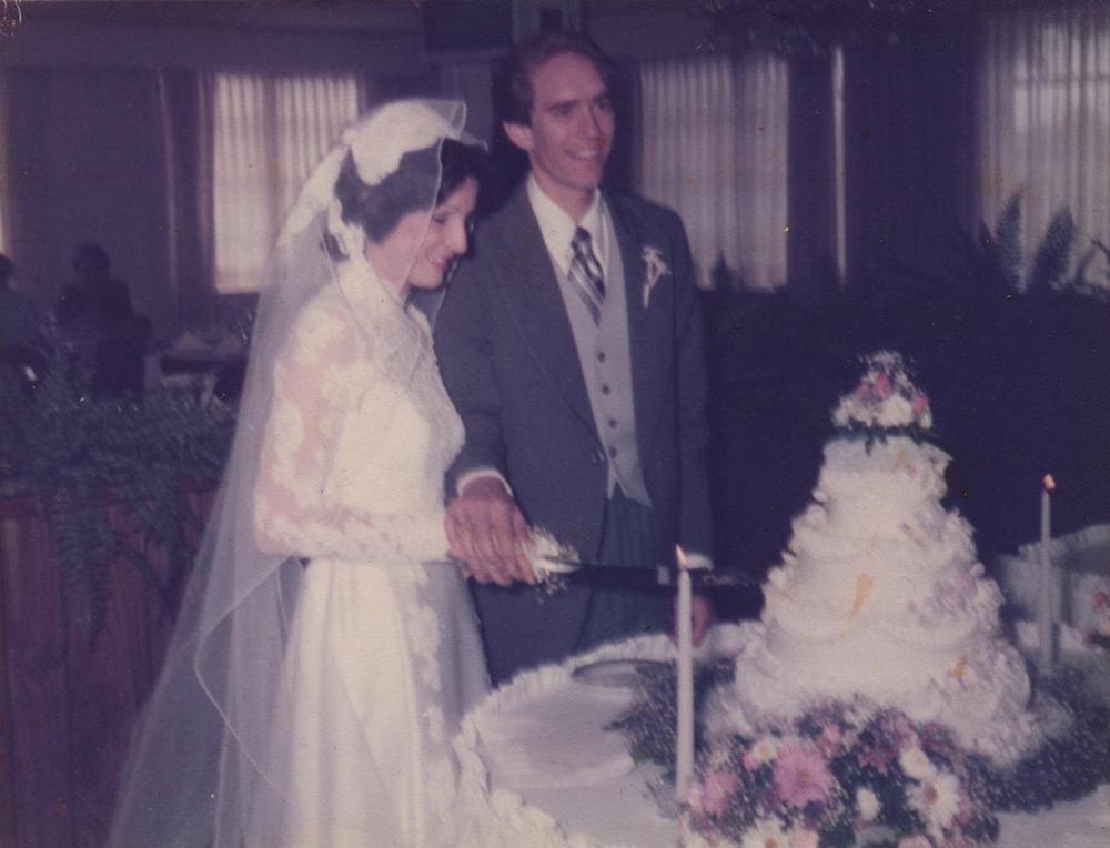 Nancy & Jim cutting the cake at their wedding