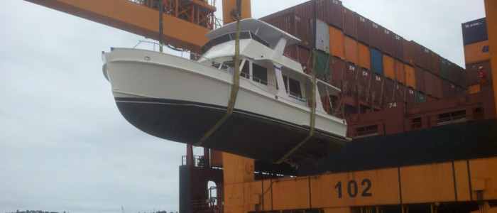 A Grand Banks yacht being offloaded from a shipping vessel.