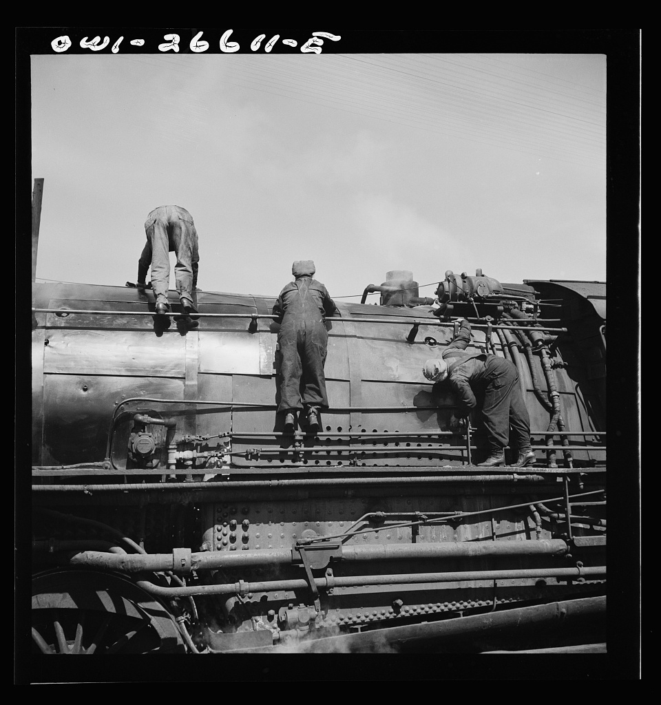 Women wipers of the Chicago Northwestern cleaning one of the giant freight locomotives.   Source