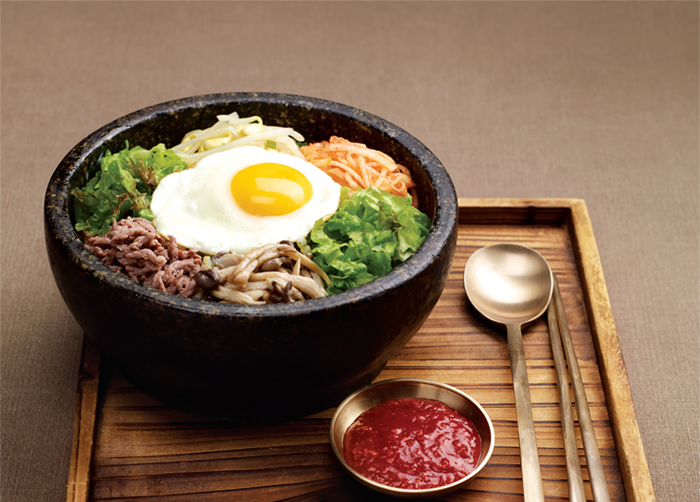 Bibimbap. Cooked rice served with fresh and seasoned vegetables, minced raw beef and chili paste.