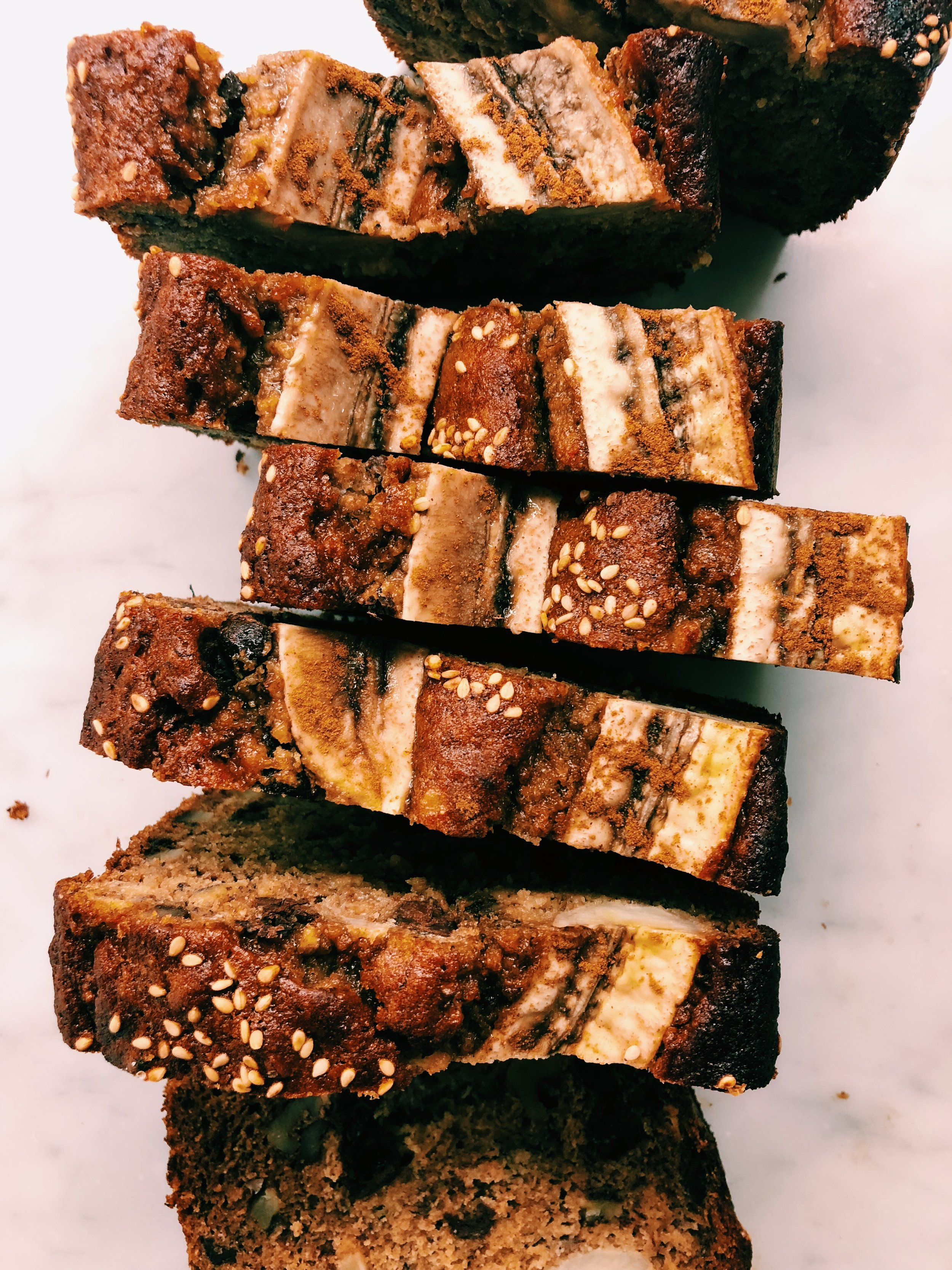 CHOCOLATE CHIP PECAN TAHINI BANANA BREAD - INGREDIENTS1/4 cup tahini1/4 cup honey (I used Wedderspoon K-factor 16 Manuka Honey)1/4 cup olive oil1/4 cup coconut sugar2 eggs4 very ripe, large bananas, plus one slightly ripe banana to halve on top1 1/2 tsp baking soda1 1/2 tsp vanilla1 cup dairy free chocolate chips3/4 cup almond flour1/4 cup gluten free flour, Bob's Red Mill makes a good one1/2 cup chopped pecans (optional)Sesame seeds and cinnamon for sprinkling on top (optional)