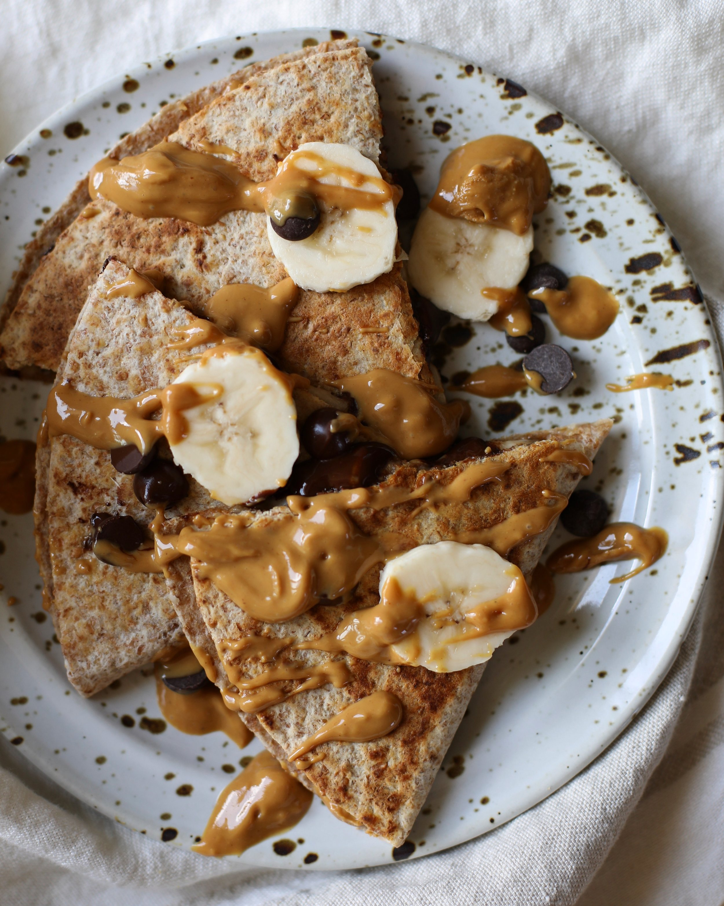 PEANUT BUTTER CHOCOLATE CHIP QUESADILLAS - INGREDIENTS2 sprouted whole grain tortillas 2 tablespoons creamy peanut butter1 banana2-3 tablespoons dairy free chocolate chips