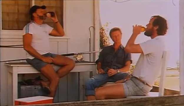 A still from an old Emu Export TV advert showing mates enjoying a bottle after a hard day fishing.