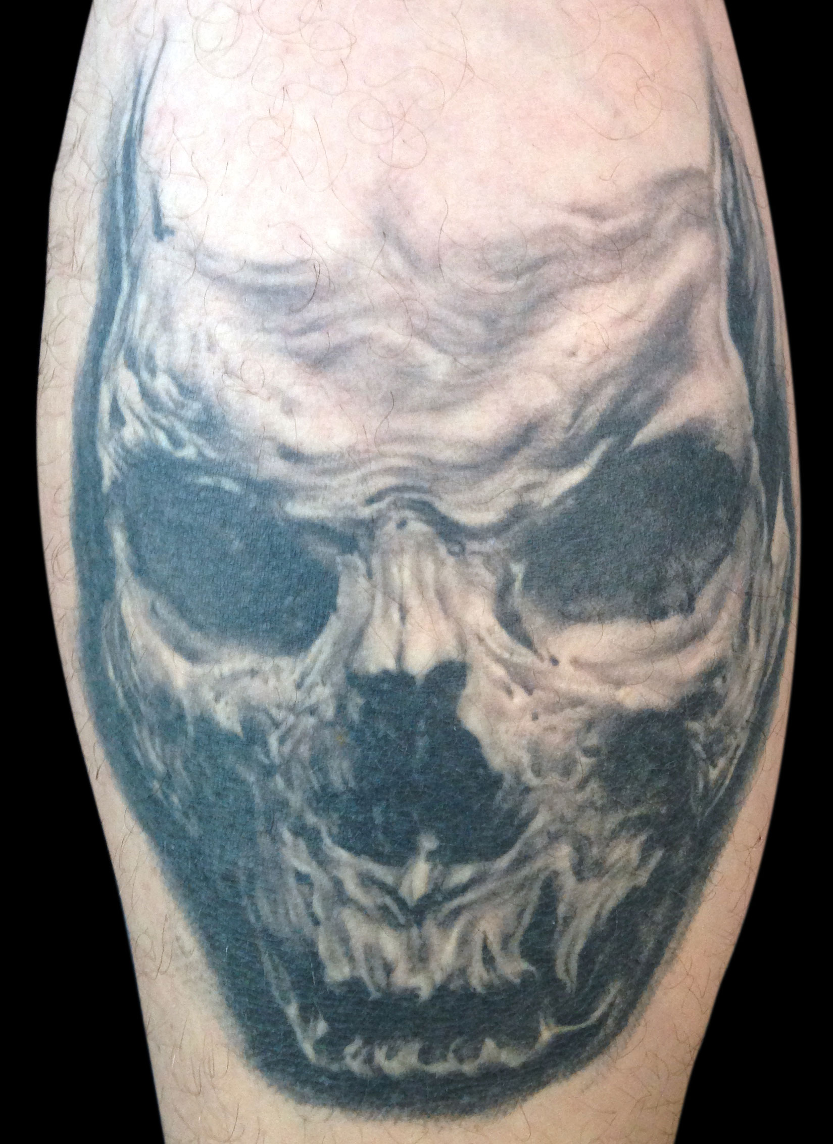 Black and Grey Horror Skull Tattoo on Rico Schinkel, (healed first session) on calf