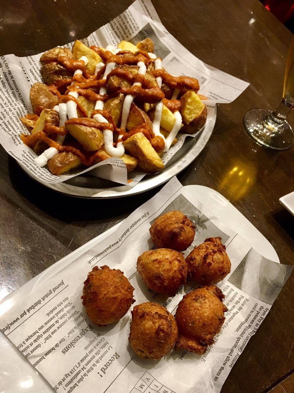 Top left: Patatas bravas, a staple tapas served across Spain. Fried potato wedges with aioli and spicy tomato sauce. Bottom right: another dish of fried croquetas, with a different filling.