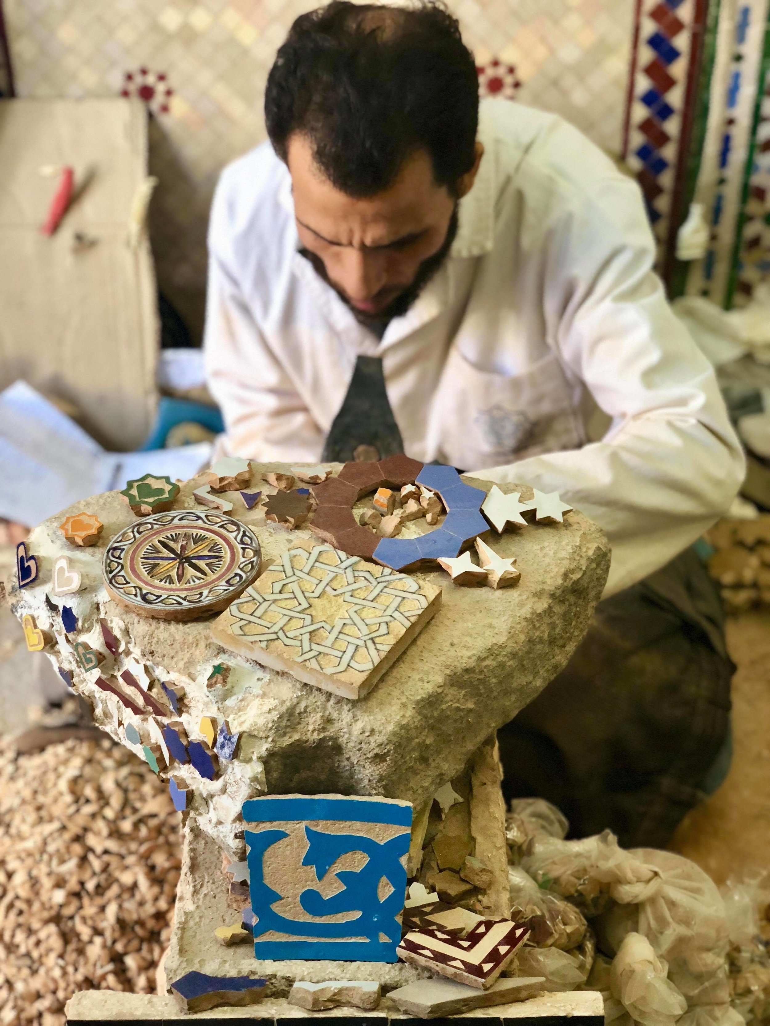 Mosaic pieces are then laid with their glazed and colored sides facing down, requiring the artisan laying out the design to memorize the mosaic's layout and be able to assemble the pieces on its flip-side.