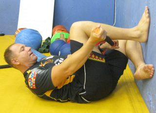 Using the Tiger Tail to roll the calves in a flexed knee closed kinetic chain position