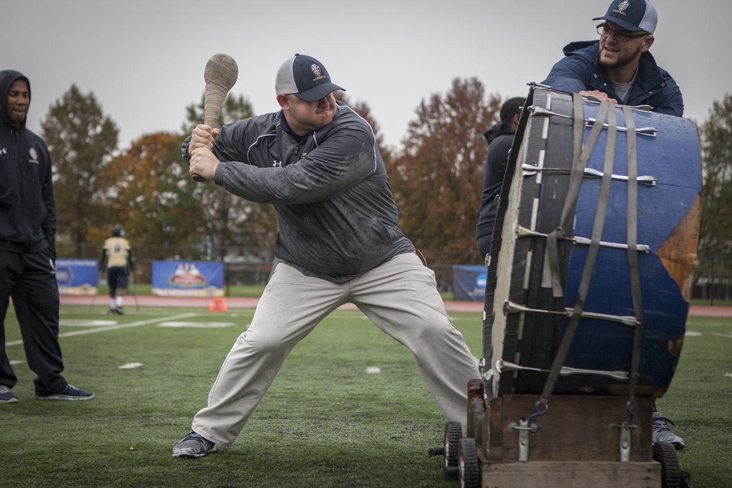 Coach Phil Endicott swings at the team's drum during a home game against Anna Maria College on November 14, 2015 at Gallaudet University. The drum is used because everyone can feel the emanating vibrations and it's used during practices and games to signify important moments.