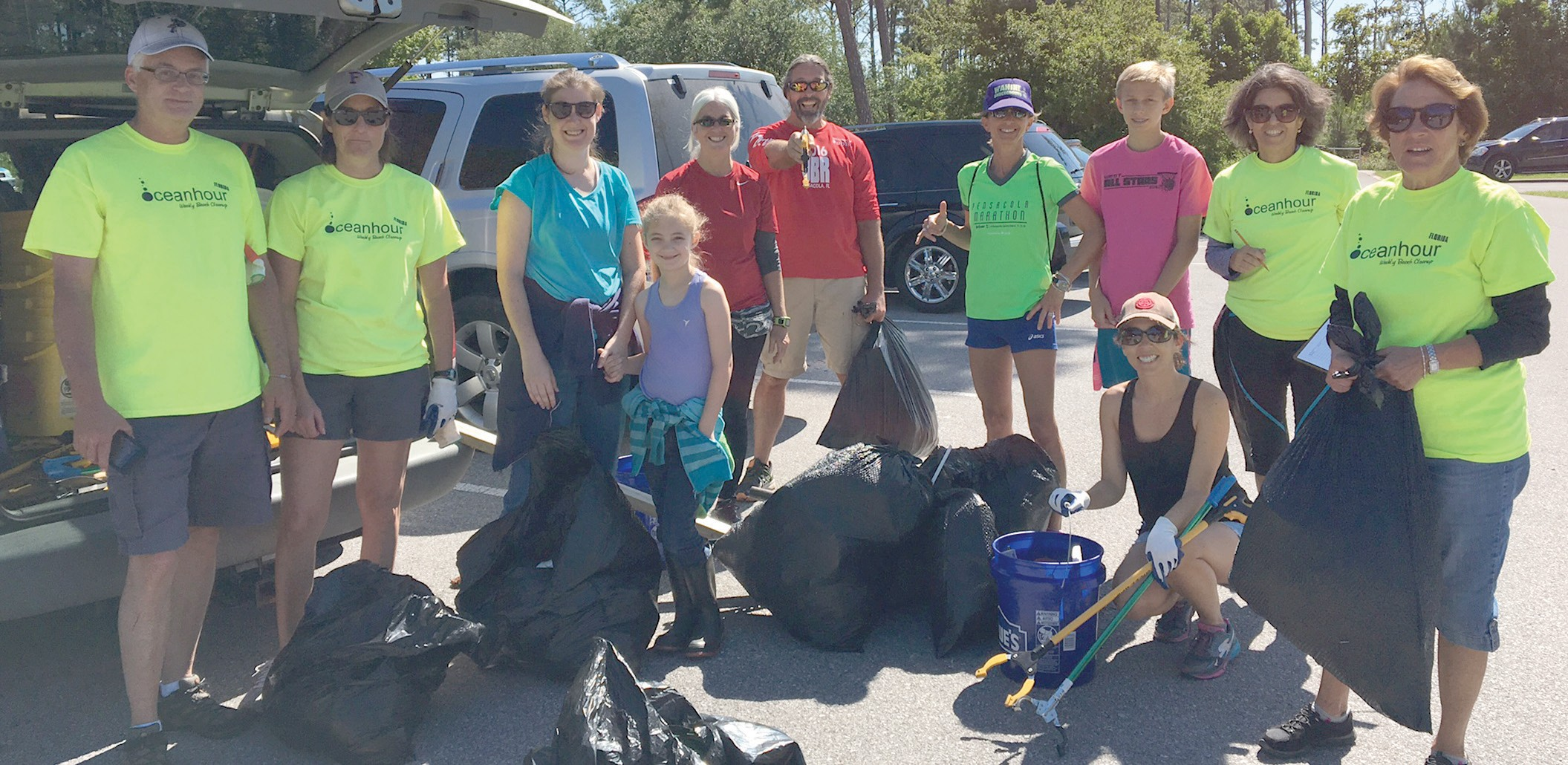 """""""Volunteers with Ocean Hour gather after combing the Naval Live Oaks Seashore in Gulf Breeze for litter and collecting it in trash bags"""" - Lisa Newell."""