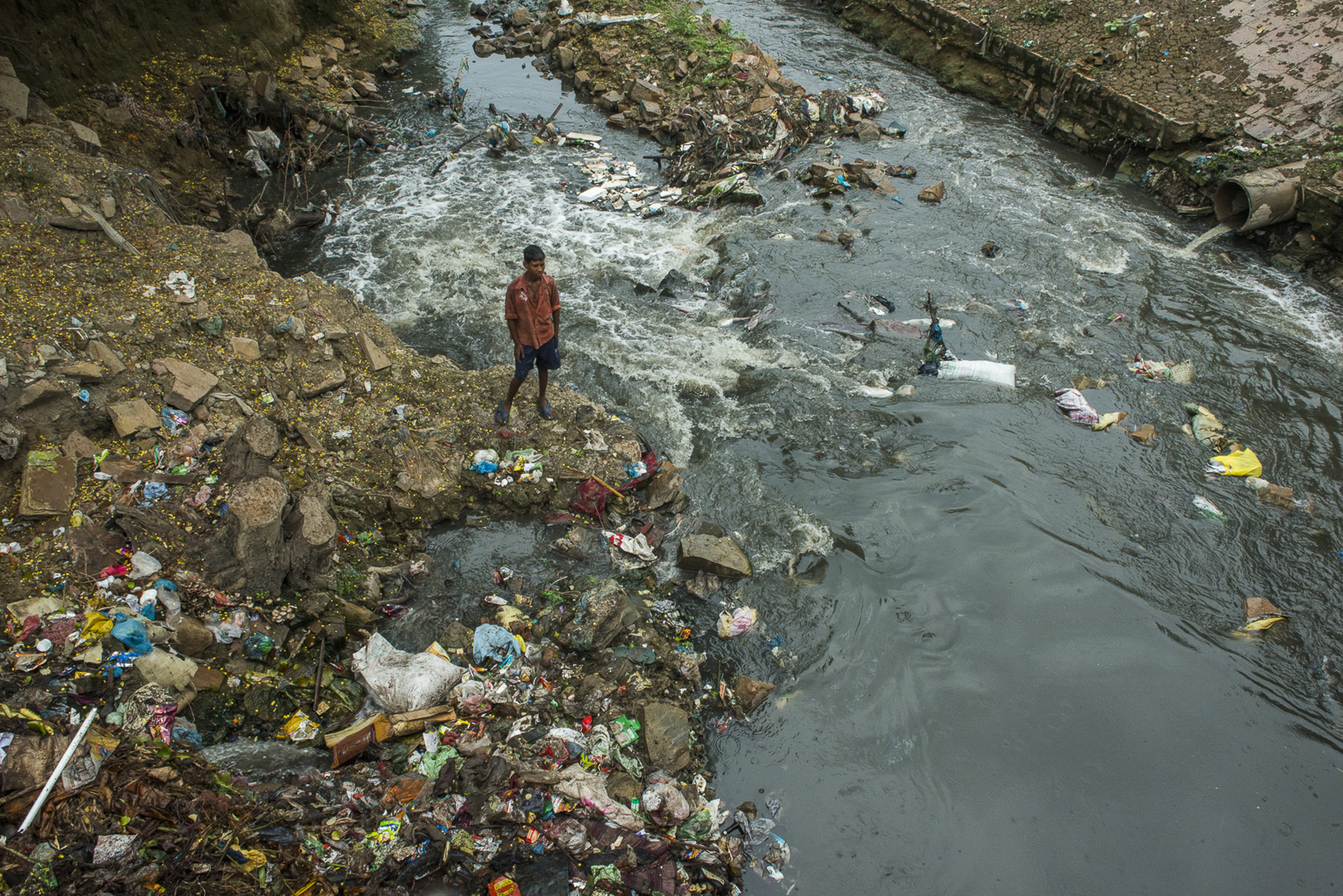 A young man stands amidst a pile of trash in a sewage-tributary to the Ganges at Varanasi, Uttar Pradesh, India. Photo © Pete McBride.