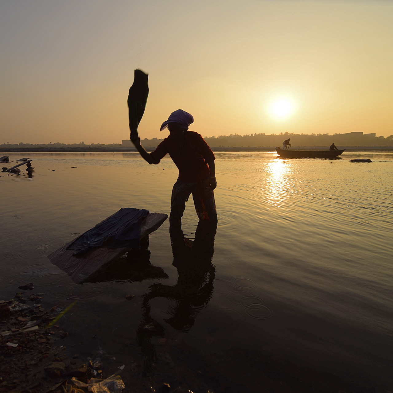 A woman washed clothing at Dhobi ghat on the Yamuna River near the Taj Mahal, Agra, India.  Photo © Jake Norton.