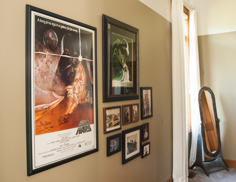 A treasured, vintage signed Star Wars poster is the star of this gallery wall. Walls are painted two-thirds of the way up, as is common in Europe, a reminder of their travels back in the day.