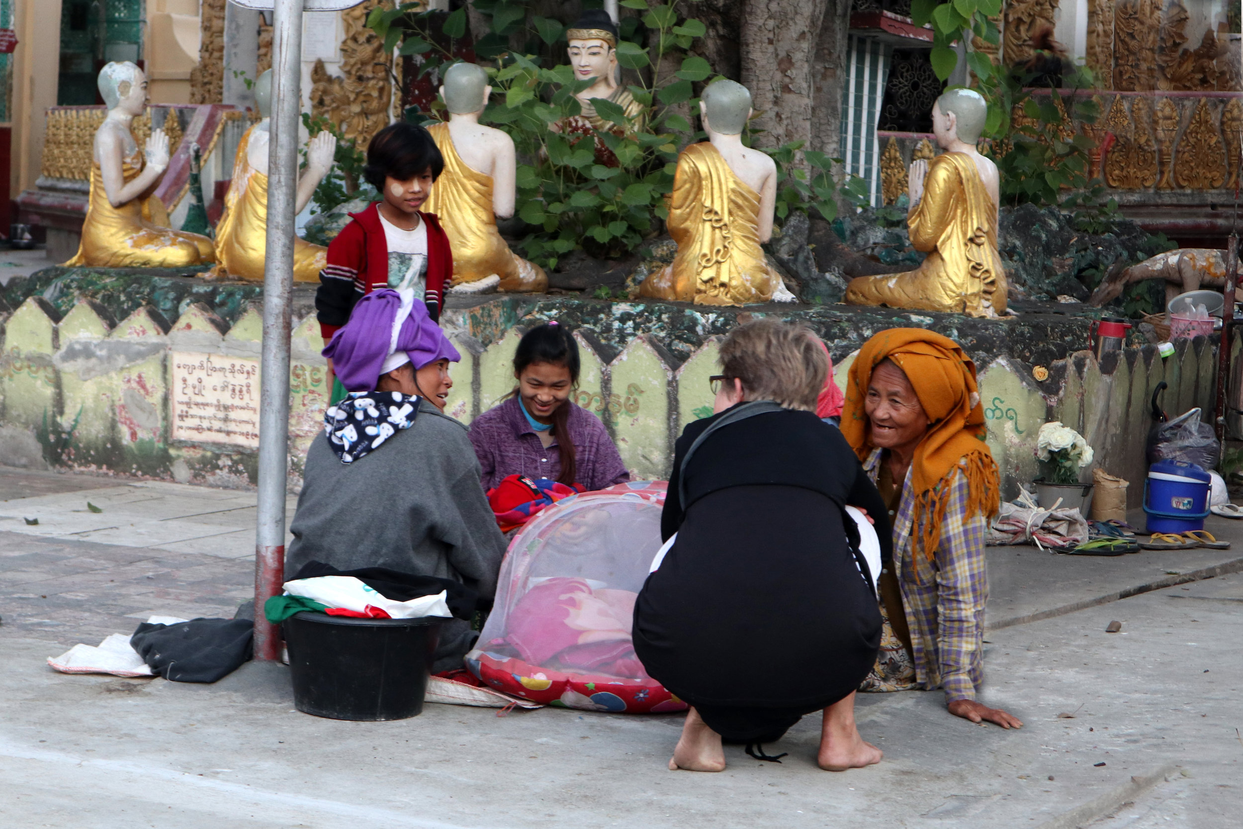 These Mandalay women -four generations, including newborn twins - appeared to be living at the temple. They could have benefitted from a bit of stupa gold.