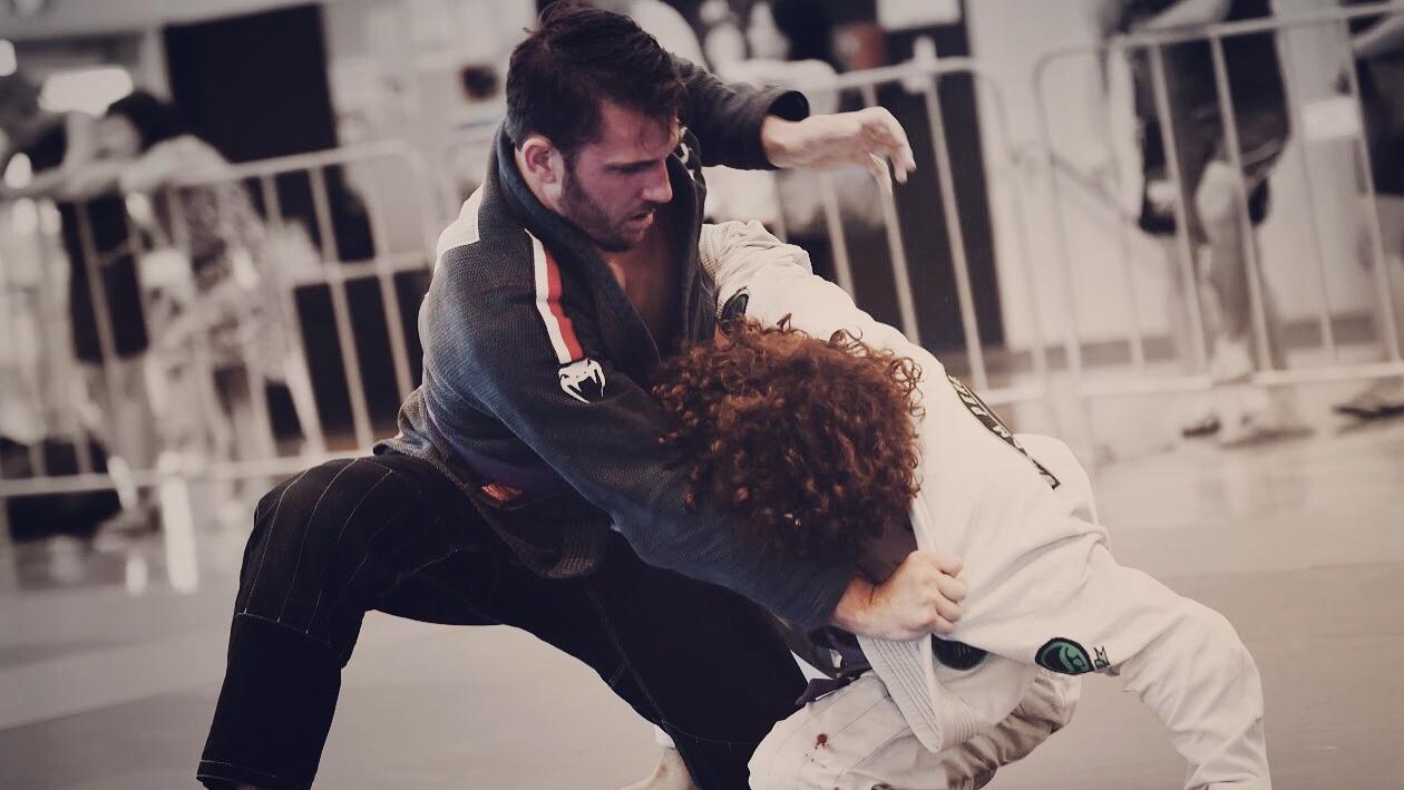 Rhys Jack grappling a competitor with a gi on in a Brazilian Jiu Jitsu tournament.