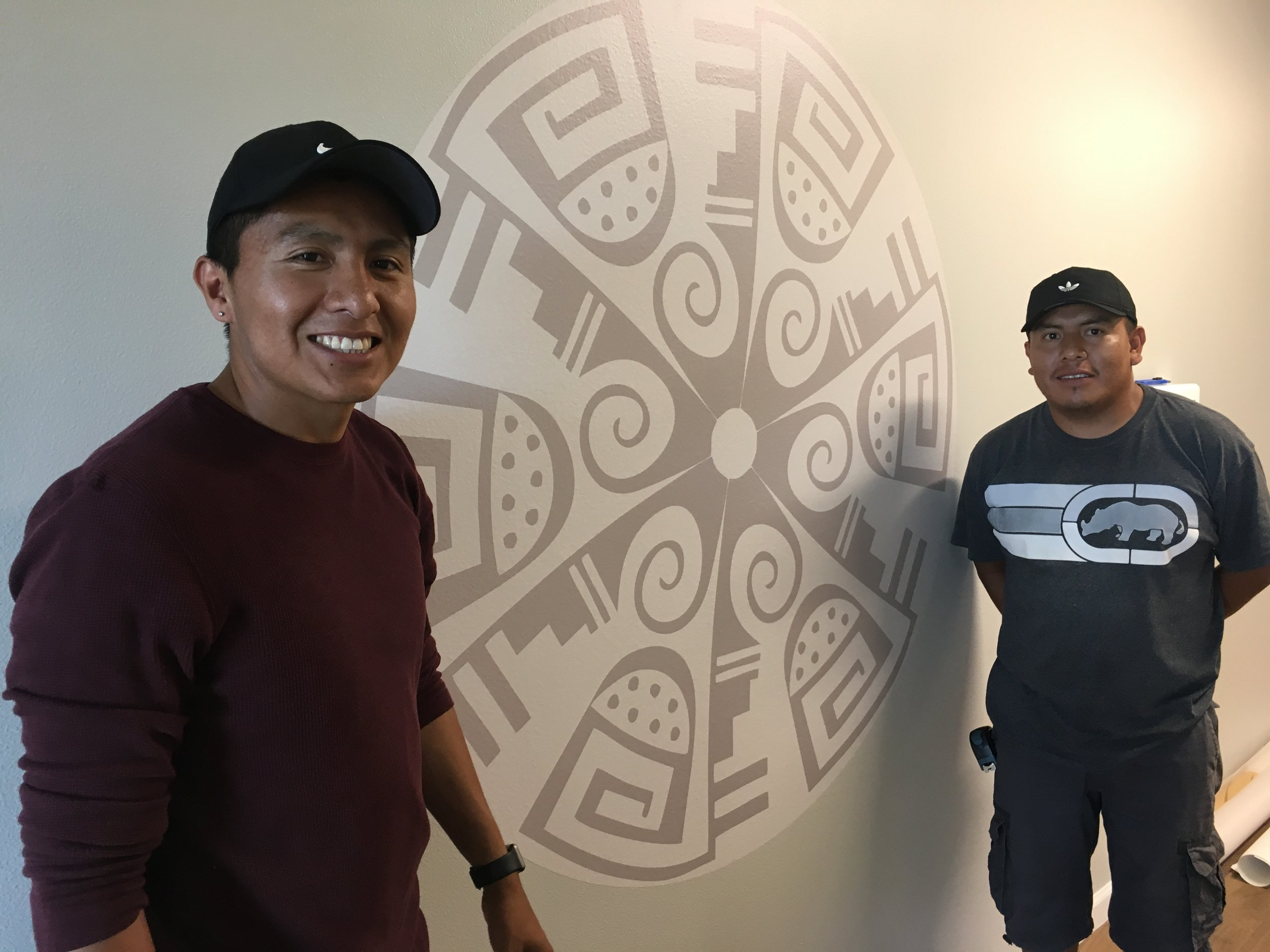 Michael Adams (left) and helper with his Hopi art mural