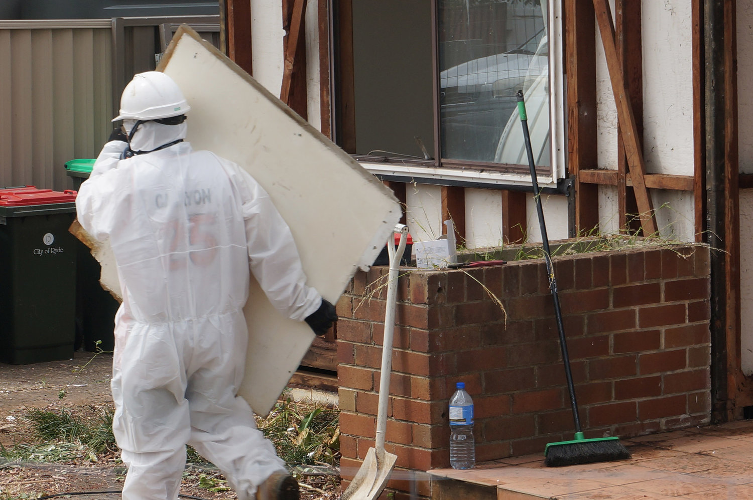Asbestos labourer removing panel of friable asbestos.