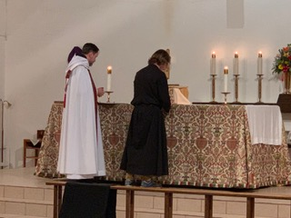 Br. Carter-Juan signs his vows. - This is traditionally done on the altar and the vows are then placed as an offering.
