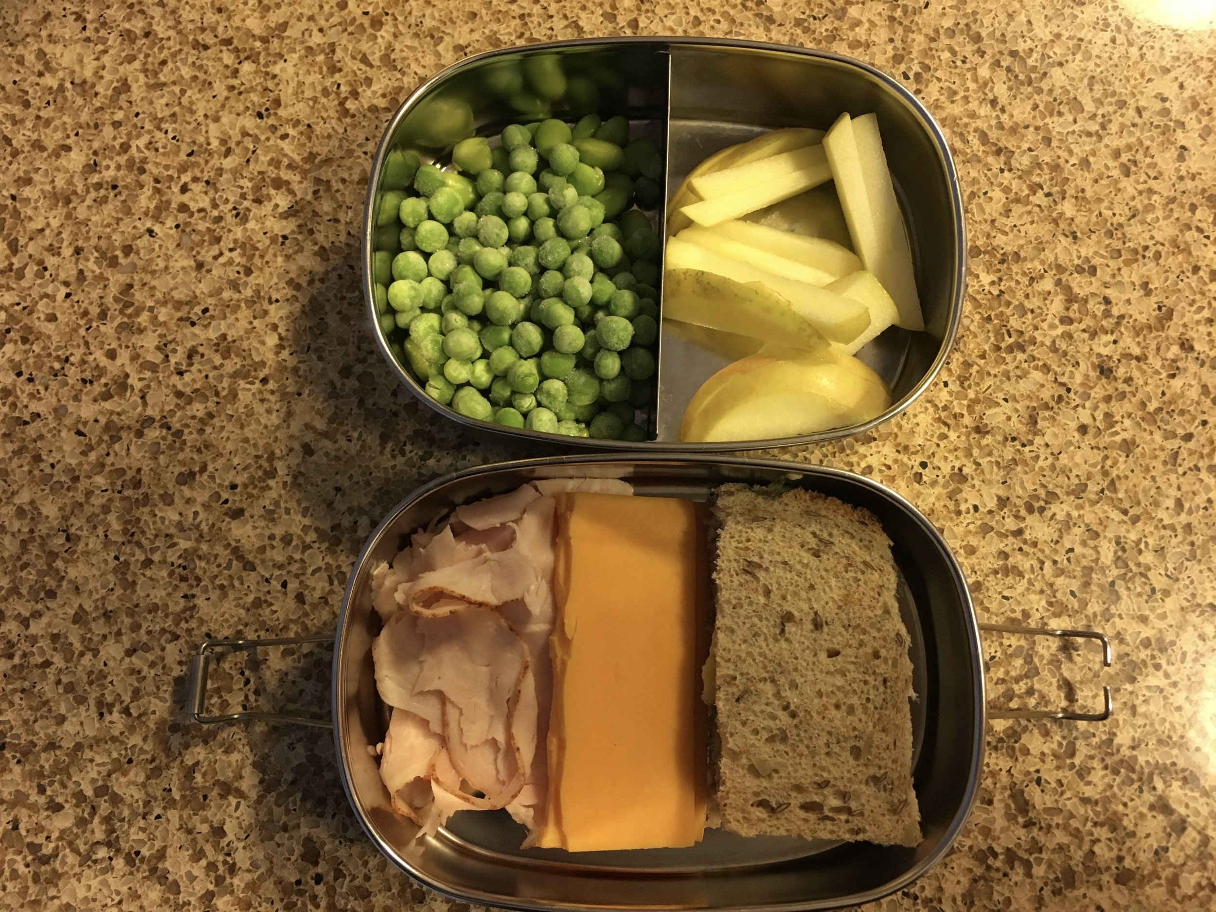 Super simple lunch. Clockwise from top left: frozen peas, sliced apple, bread, cheese and turkey