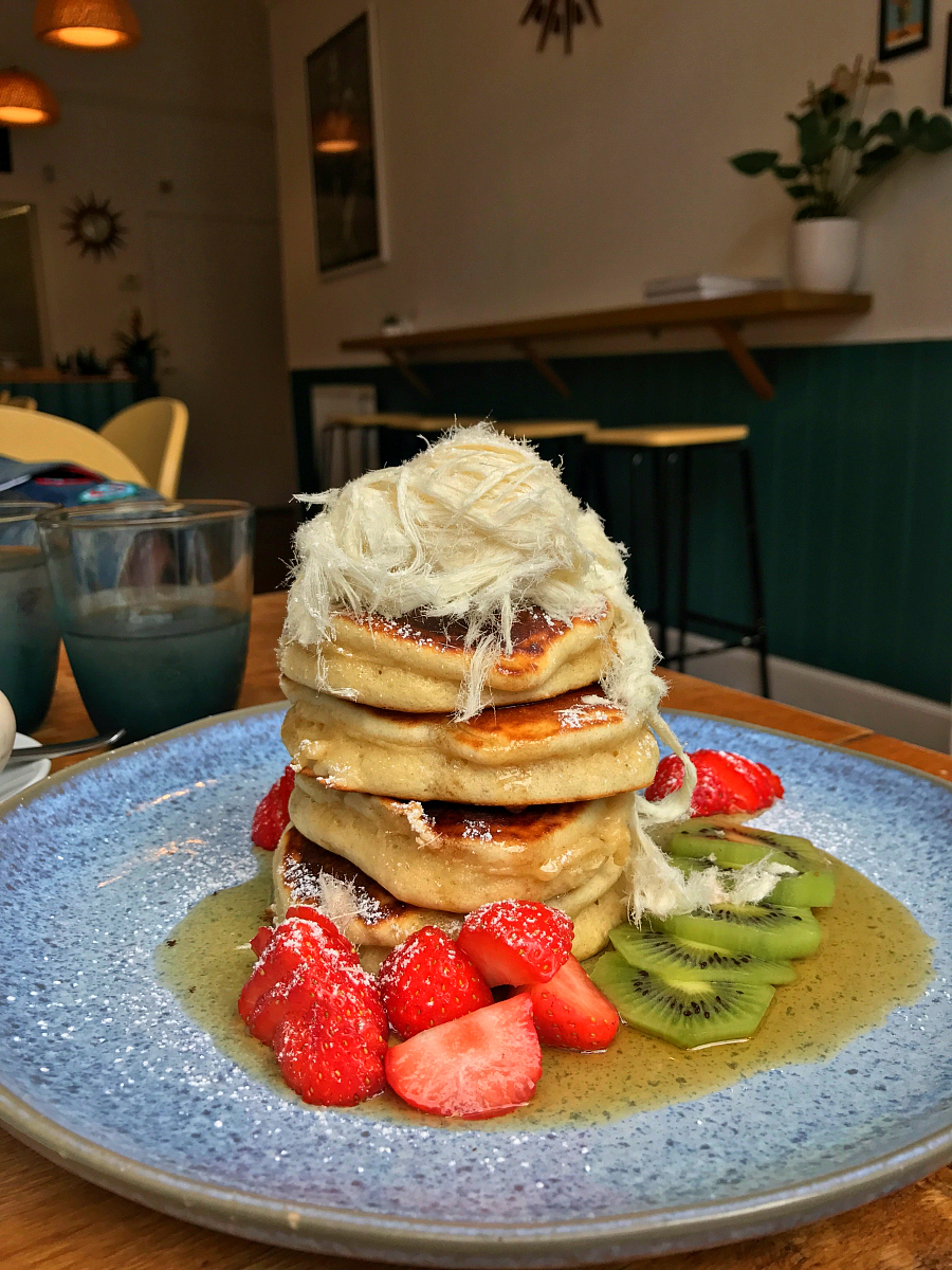 Hot cakes with strawberries, blueberries, kiwi fruit, pashmak, maple syrup