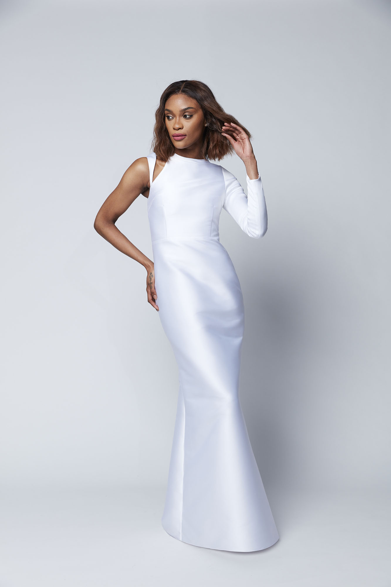 This unique asymmetric gown features an angled strap that can be worn on or off the shoulder for a stand out look.