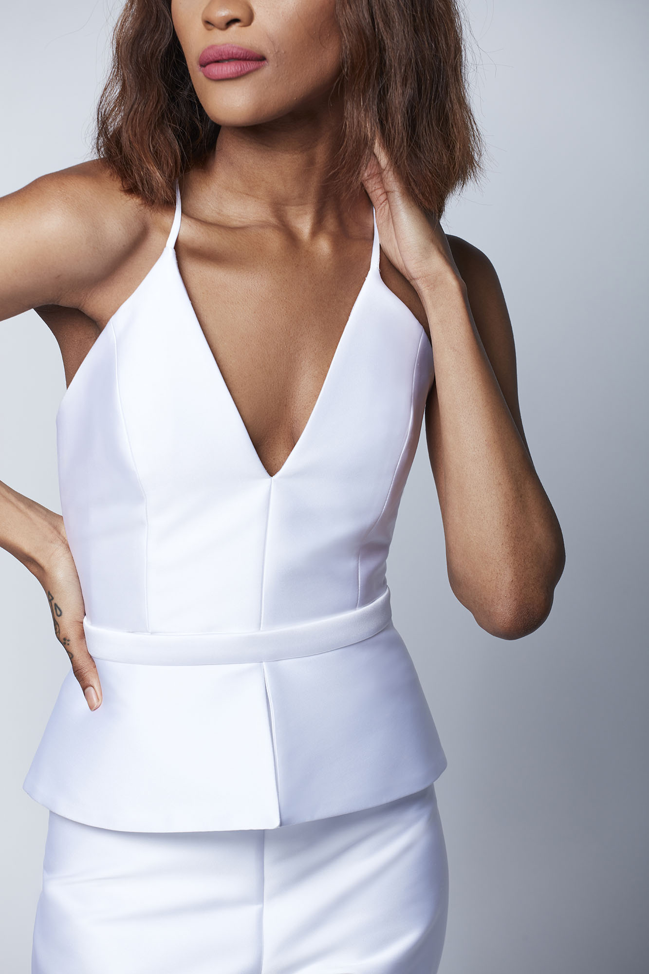 This fitted jumpsuit made from luxe Italian neoprene features a detachable peplum which is ideal for a bride seeking versatility from her wedding look.