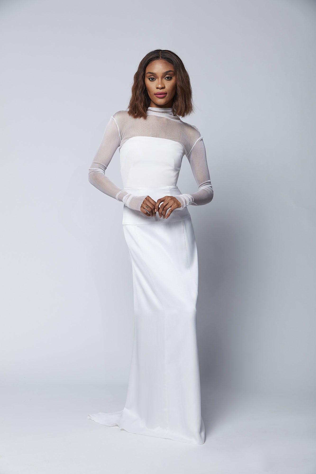 This chic silk mesh turtleneck adds drama to the clean lines of the Nivi bustier top and the drop waist Tiana column skirt. Perfect for brides who want edge and sophistication on their wedding day.