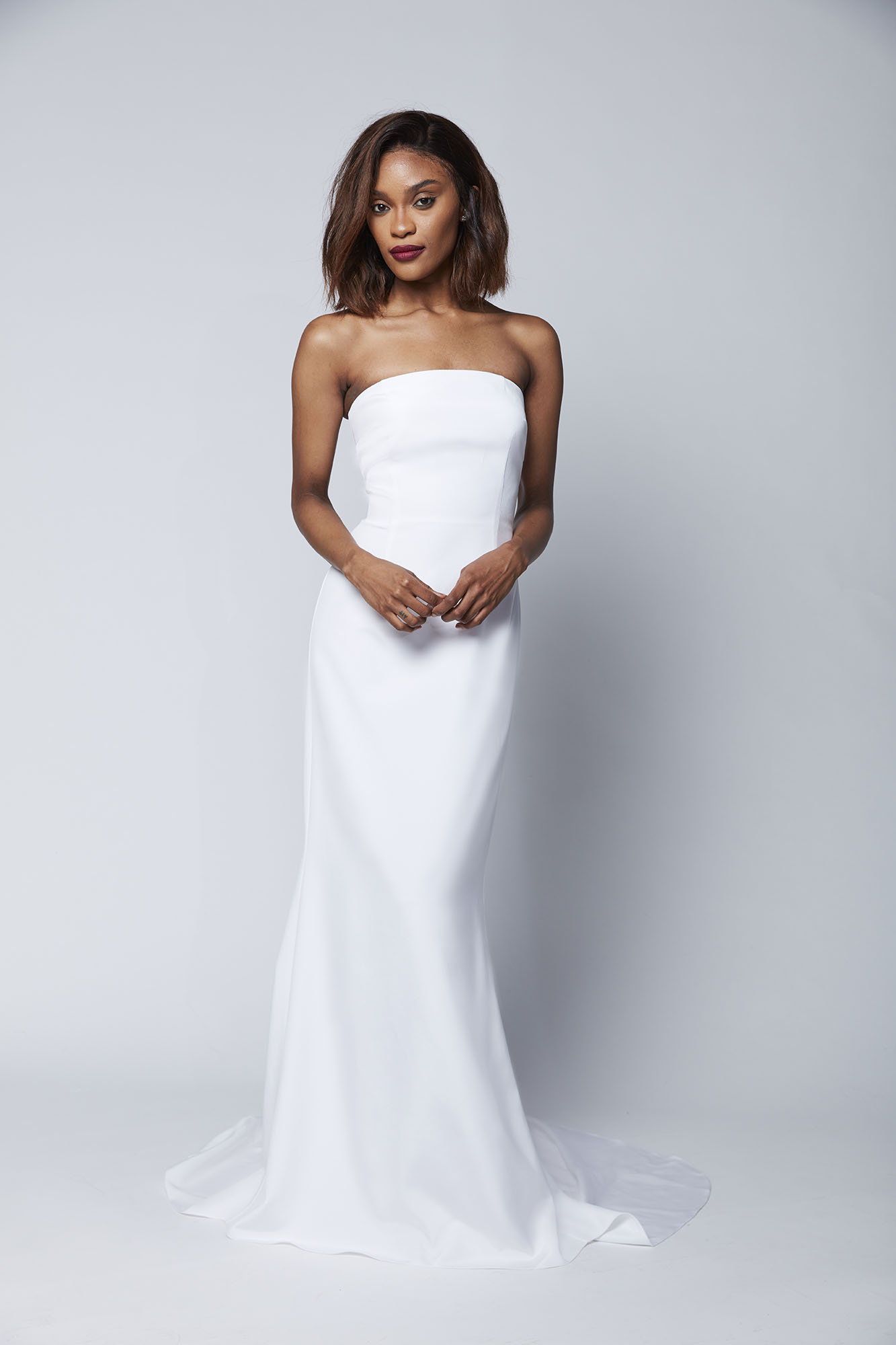 The strapless Caitlin gown with its full train is a perfect choice for the minimalist bride who wants a clean, architectural look on her wedding day.