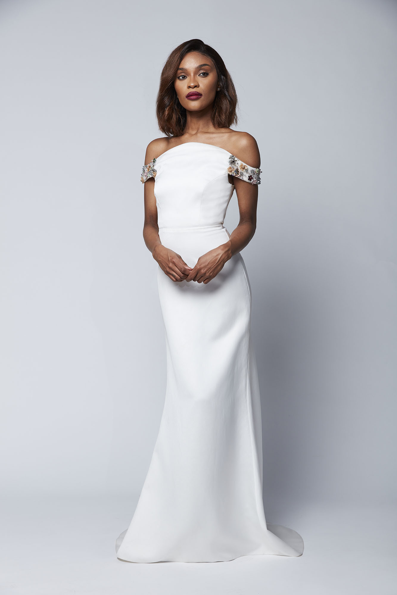 This off the shoulder gown featuring delicate, colorful embroidery is elegance embodied with its simple train and sleek fit.