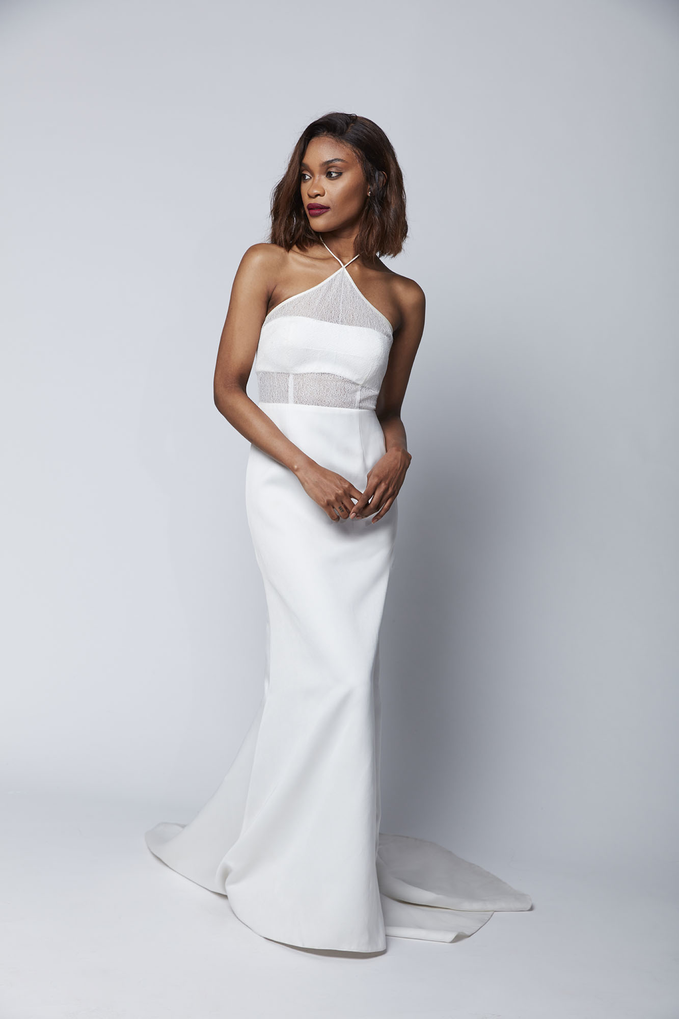 The Marisa is a sophisticated gown with a modern twist featuring a cropped bodice, cross front halter neck and fitted skirt with a dramatic train.