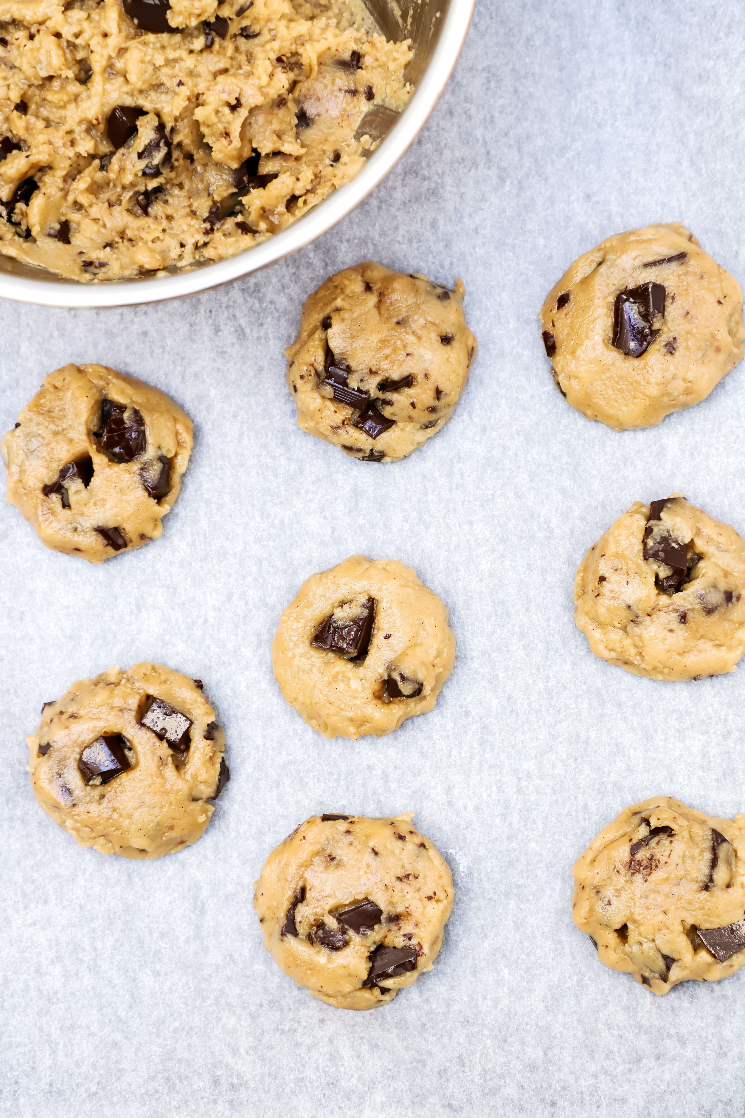 vegan and gluten-free chocolate chip cookie dough scooped out and placed on a baking sheet