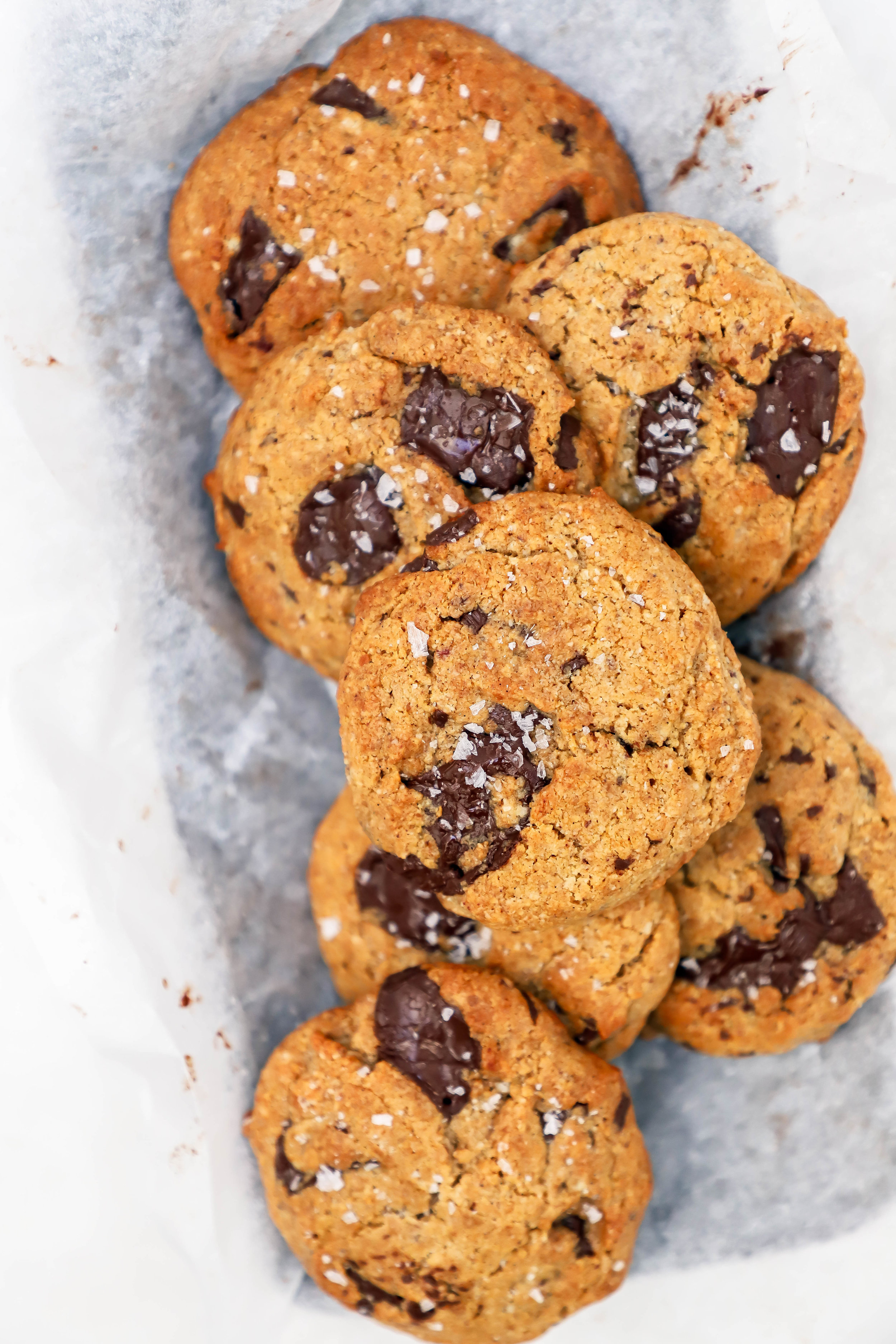 vegan and gluten-free chocolate chip cookies with tahini and coconut oil, overlapping on parchment paper