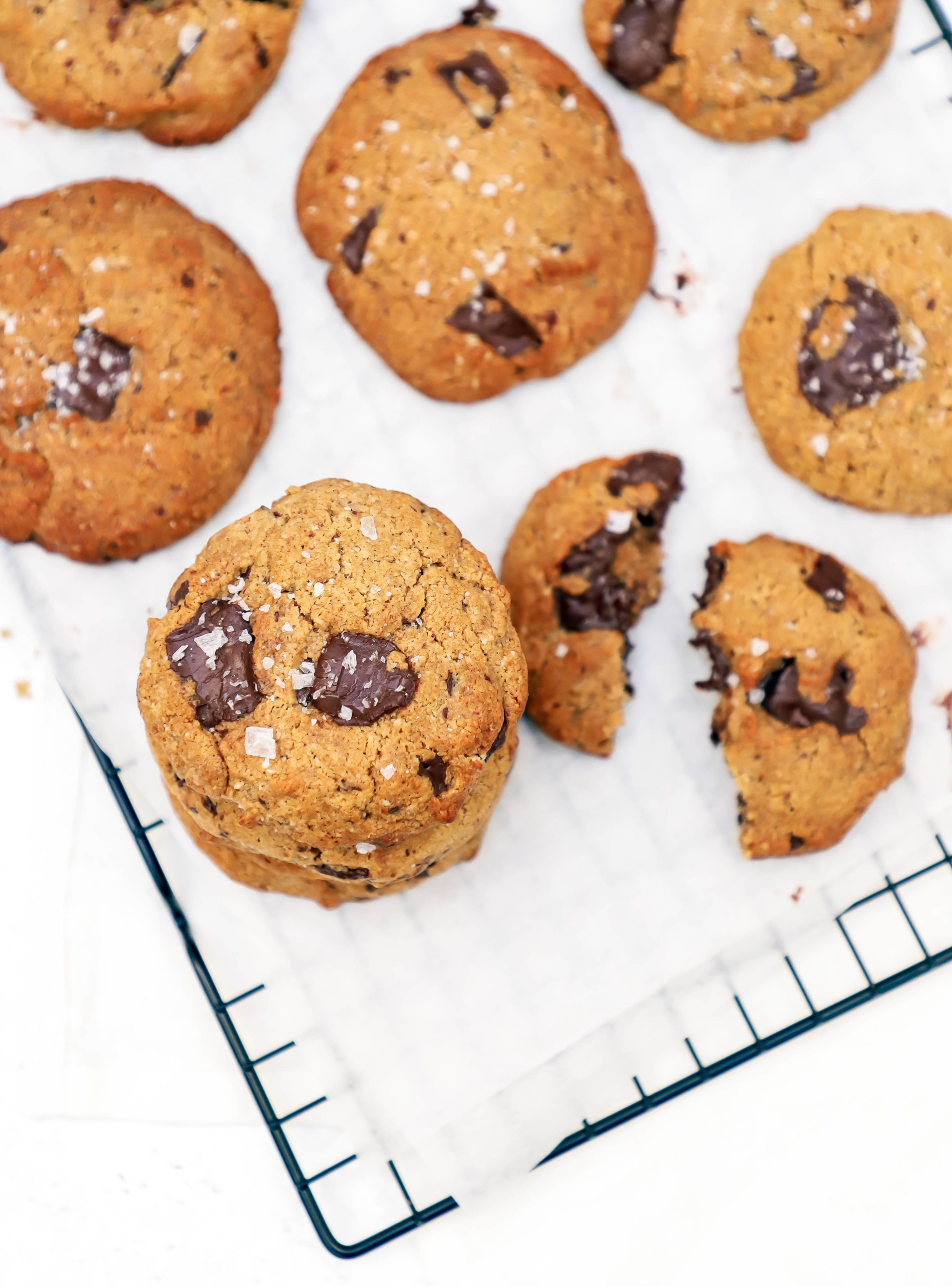 vegan+and+gluten-free+chocolate+chip+cookies+with+tahini+and+coconut+oil%2C+cooling+on+a+grid+sheet+lined+with+parchment+paper