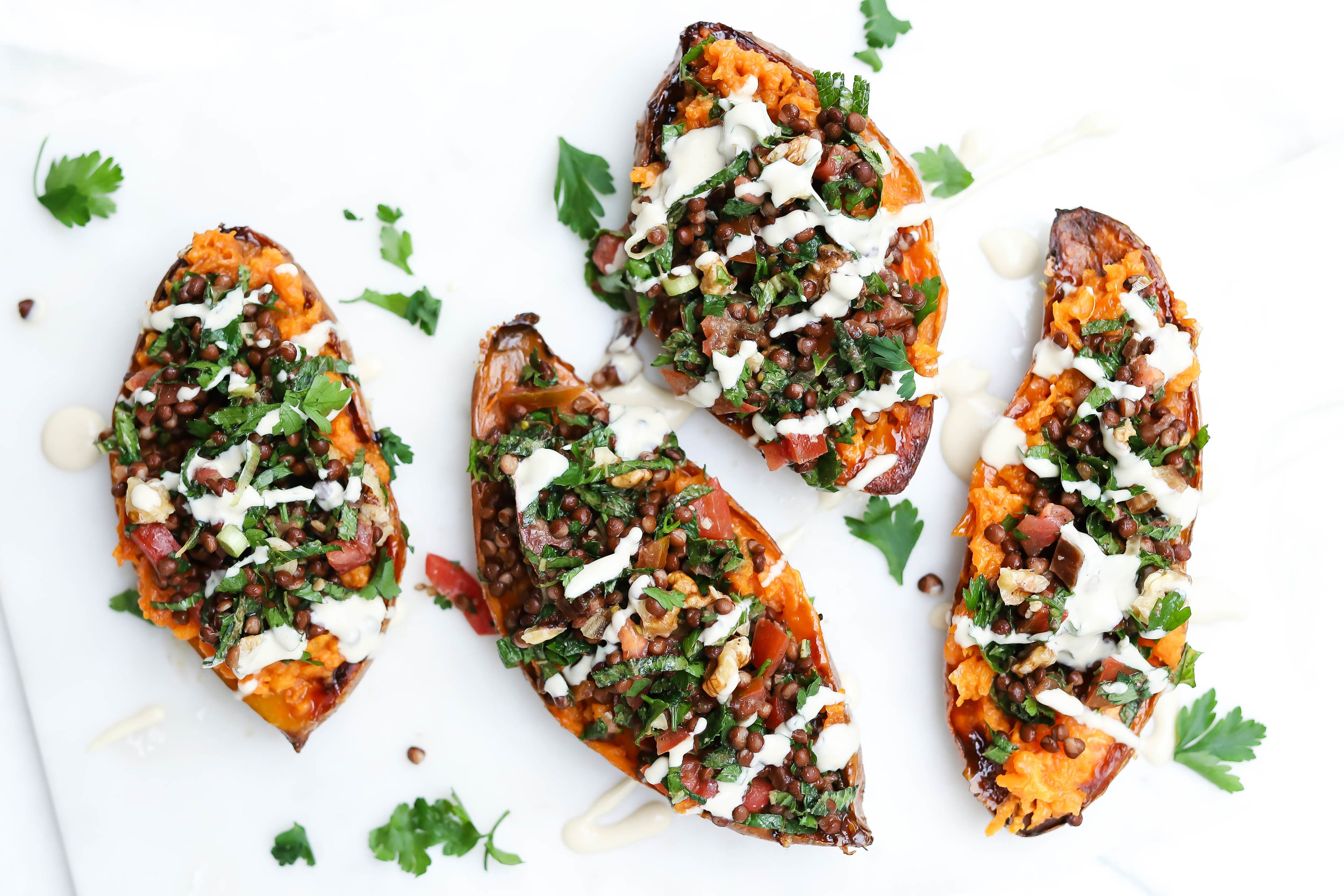 vegan and gluten-free mediterranean stuffed sweet potatoes on a marlbe board with chopped walnuts and a tahini drizzle