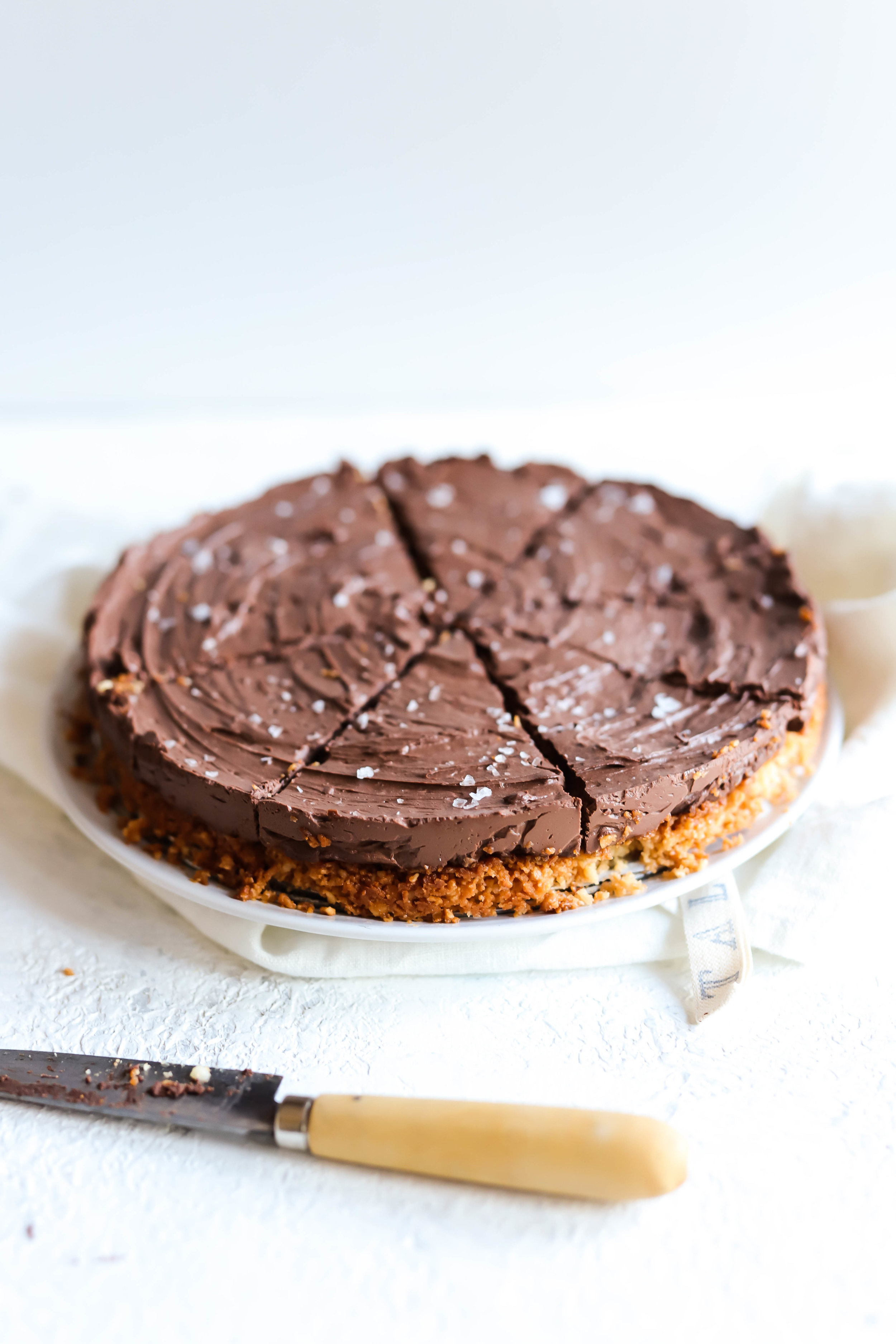 vegan and gluten-free chocolate pie sliced into eight pieces with a knife to the side