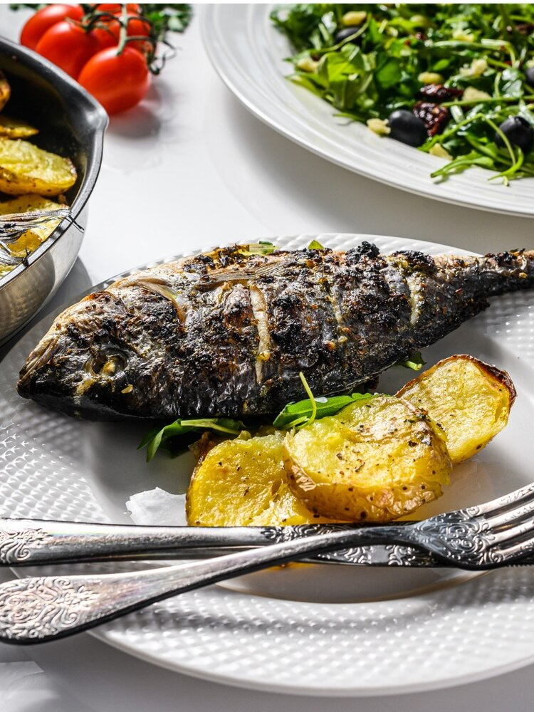 dinner-with-grilled-sea-bream-fish-arugula-salad-with-tomatoes-baked-picture-id1216807971.jpg