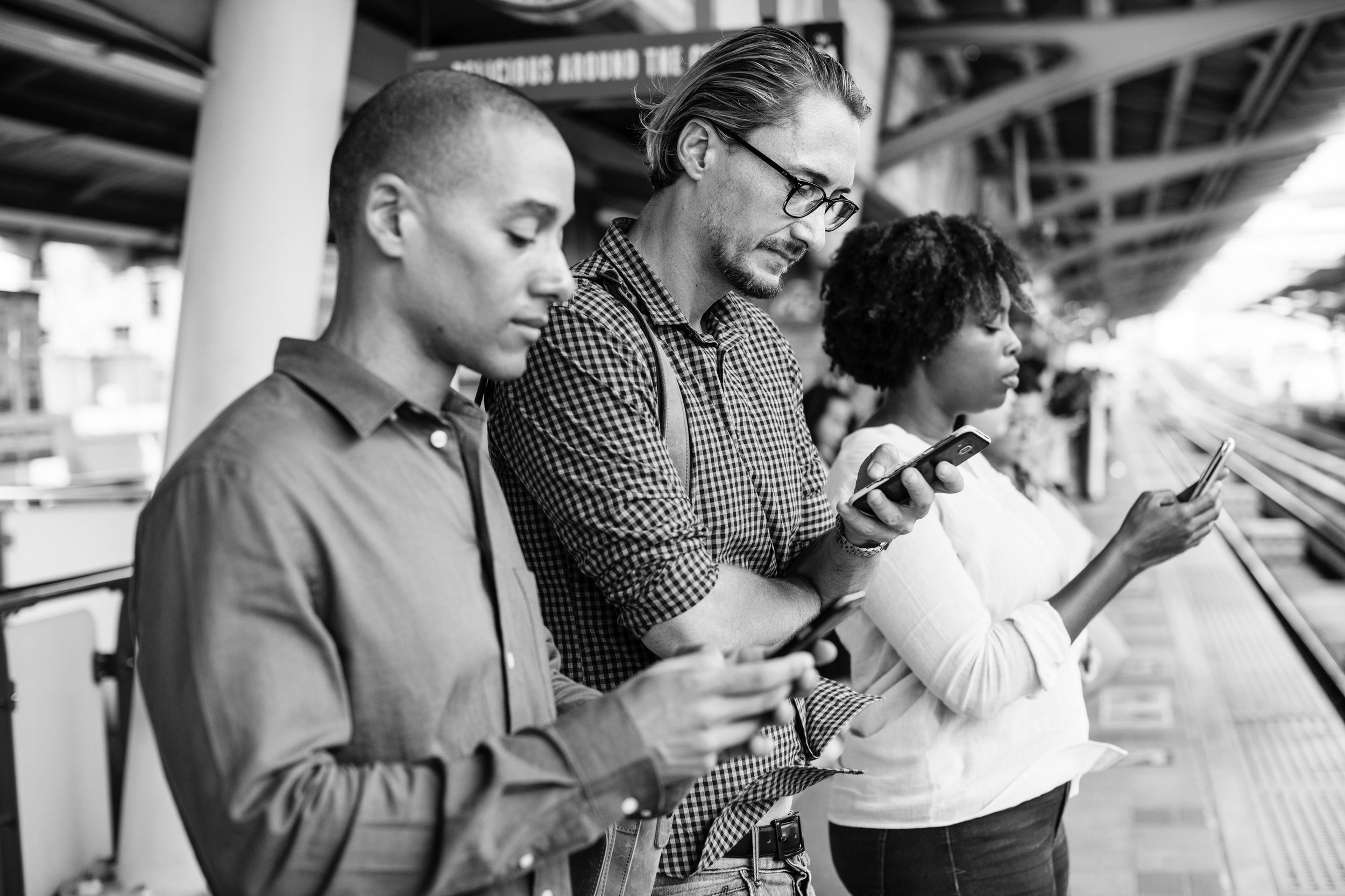 three-adults-using-smartphones-on-train-platform-bw.jpg
