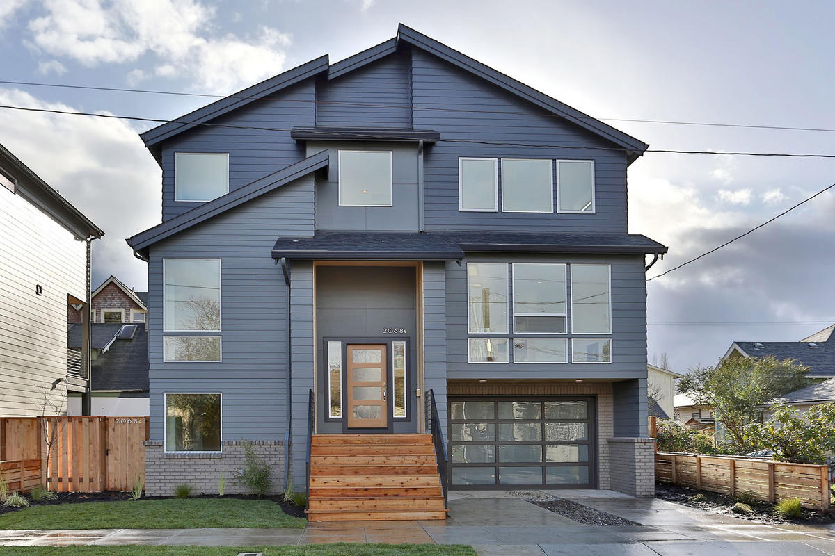 With a robust color consultation practice, we worked with both client and developer to select an exterior color palette that would accentuate the varying planes of the home while remaining subtle and refined. The addition of wood on the steps, doors, and wrapped entry adds interest and warmth.