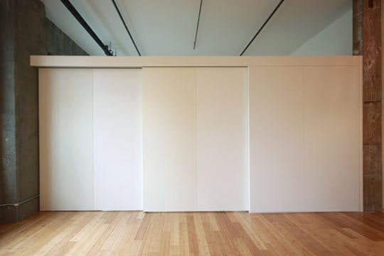 Each panel of the sliding wall is painted a slightly different tone of white to add interest.