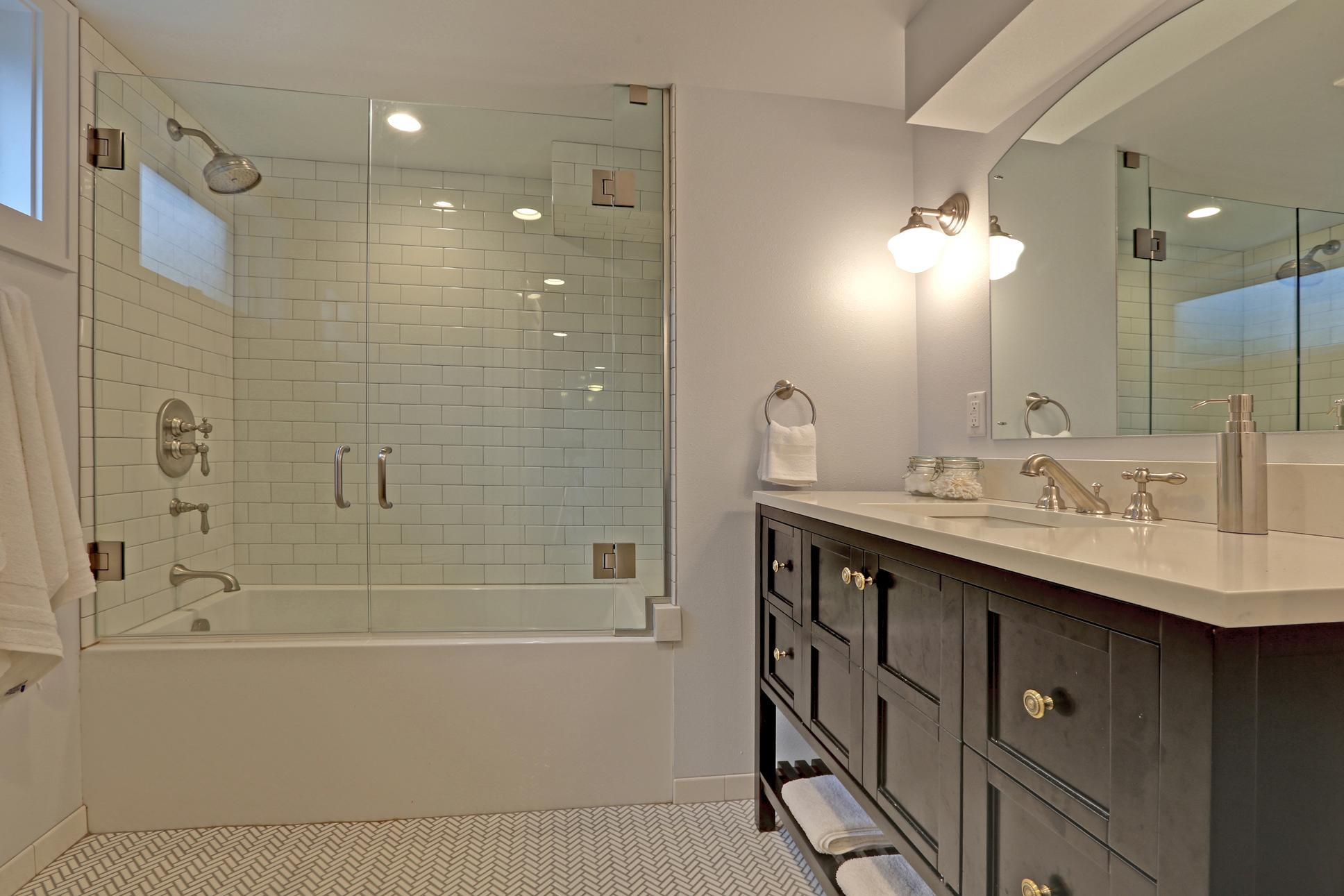 Radiant-heat herringbone Ann Sacks tile in the bathroom, Rohl fixtures, and a deep soaking tub create a destination and spa-like environment in the new bathroom.