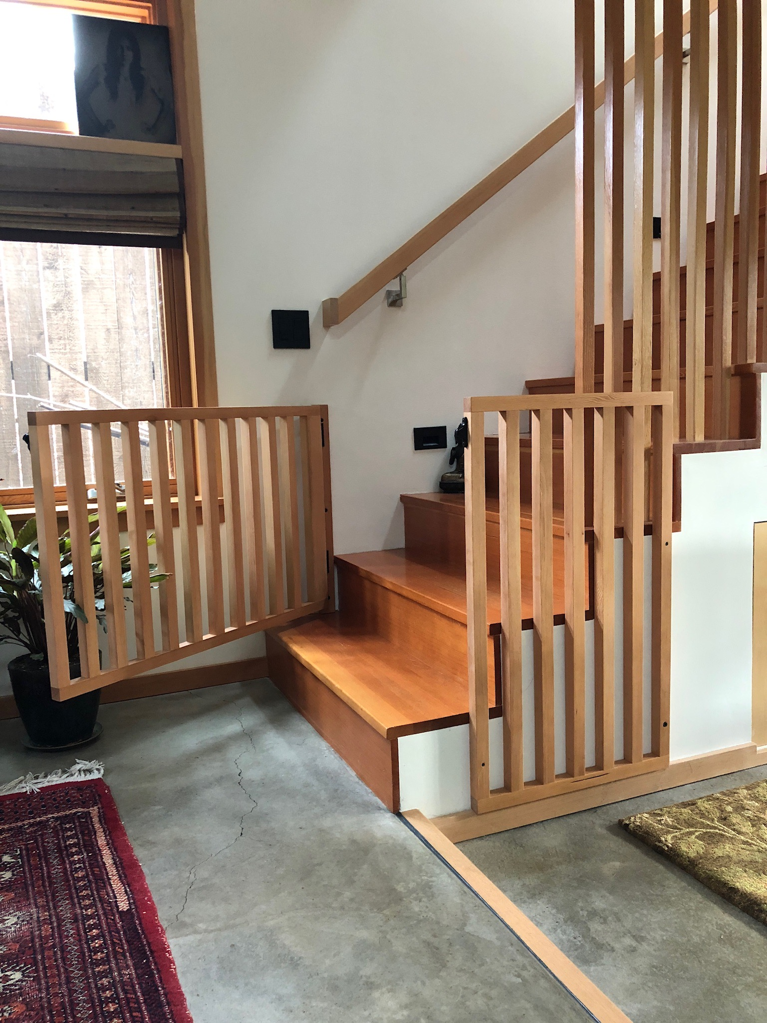 This custom baby gate was designed to perfectly align with the existing vertical slats and spacing. It is a beautiful piece that is not an eyesore. Its design blends seamlessly into the home and looks as though it was part of the original design.