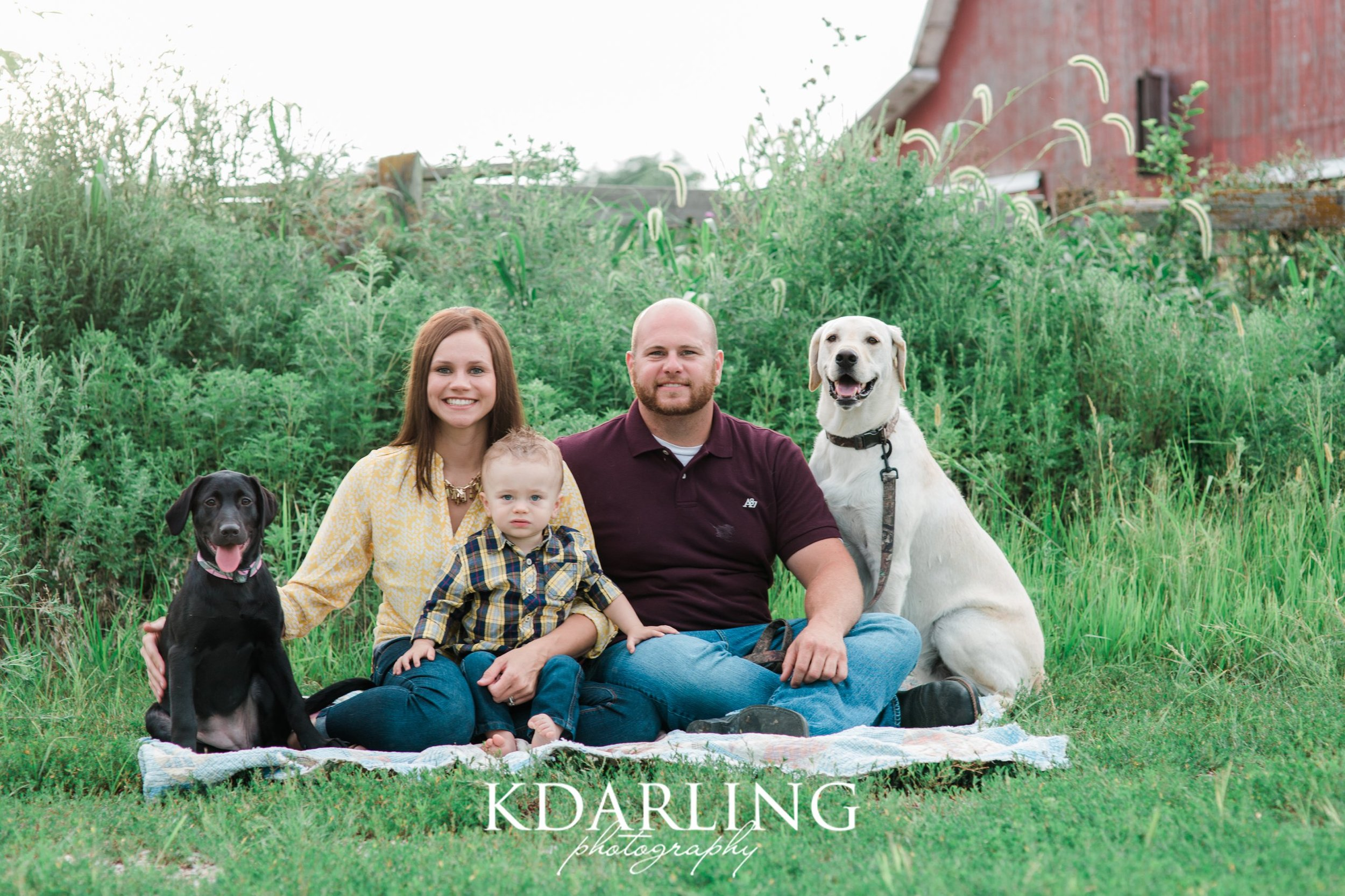 family of 3 with 2 dogs and red barn