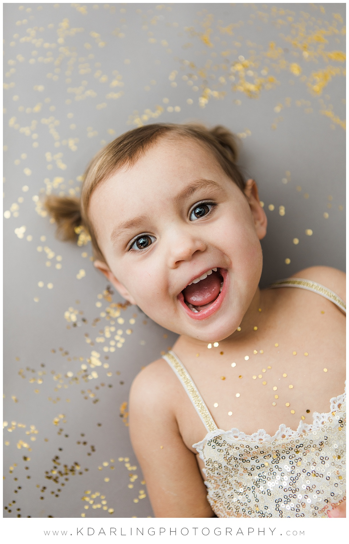 Two year old girl laying in glitter